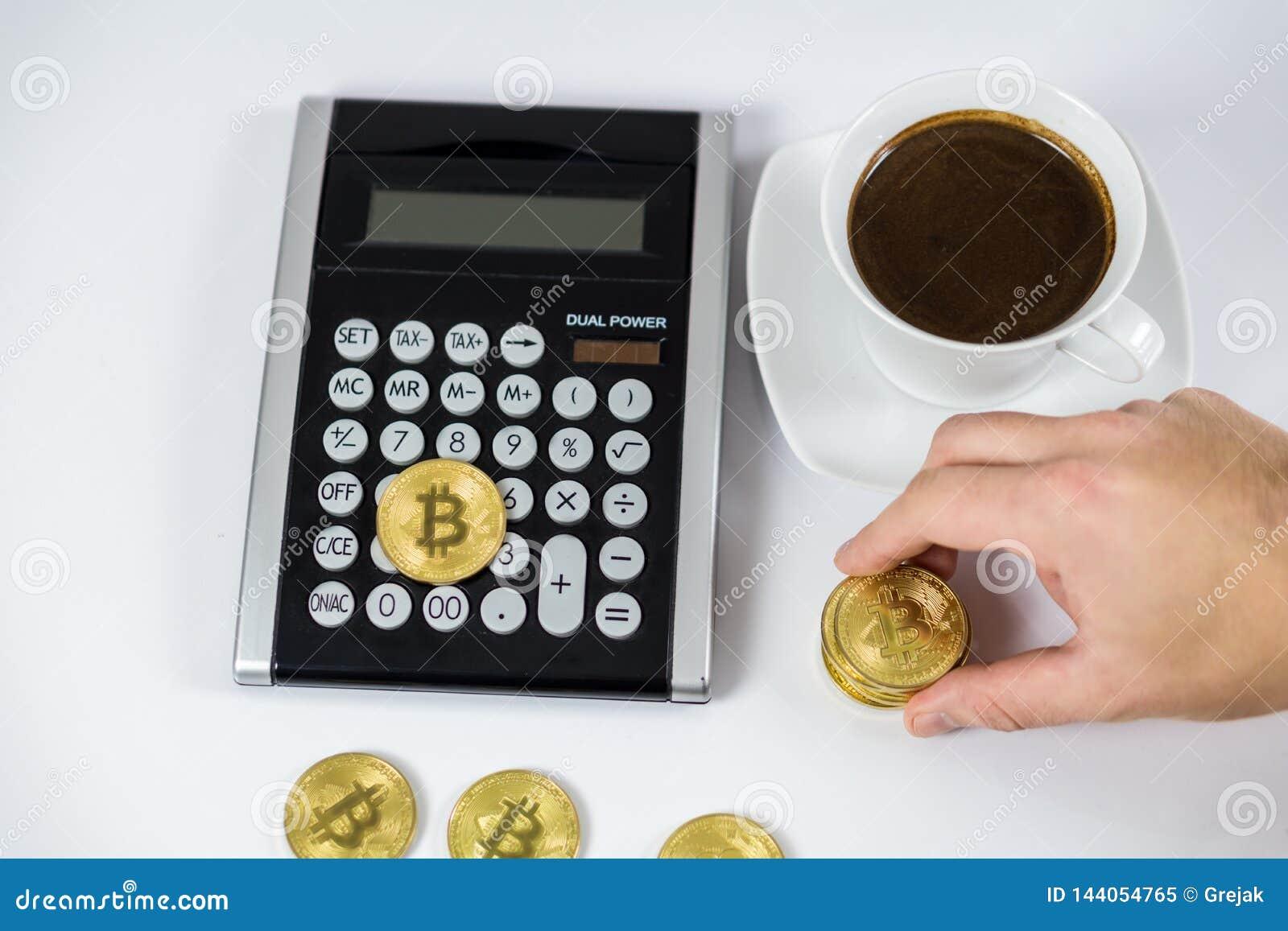 Guld- Bitcoin som rymms av handen på den svarta räknemaskinen bredvid kaffe, cryptocurrencybegrepp