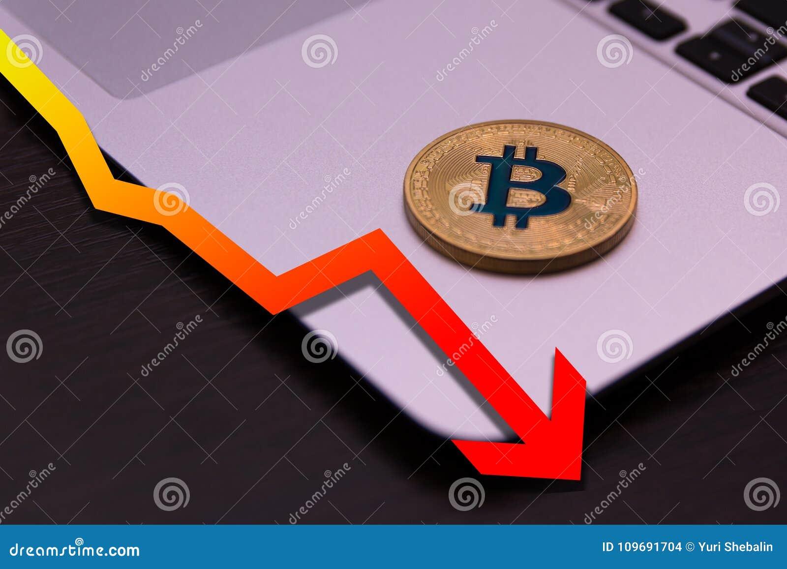 Guld- bitcoinlögn på silveranteckningsboken med den fallande röda grafen