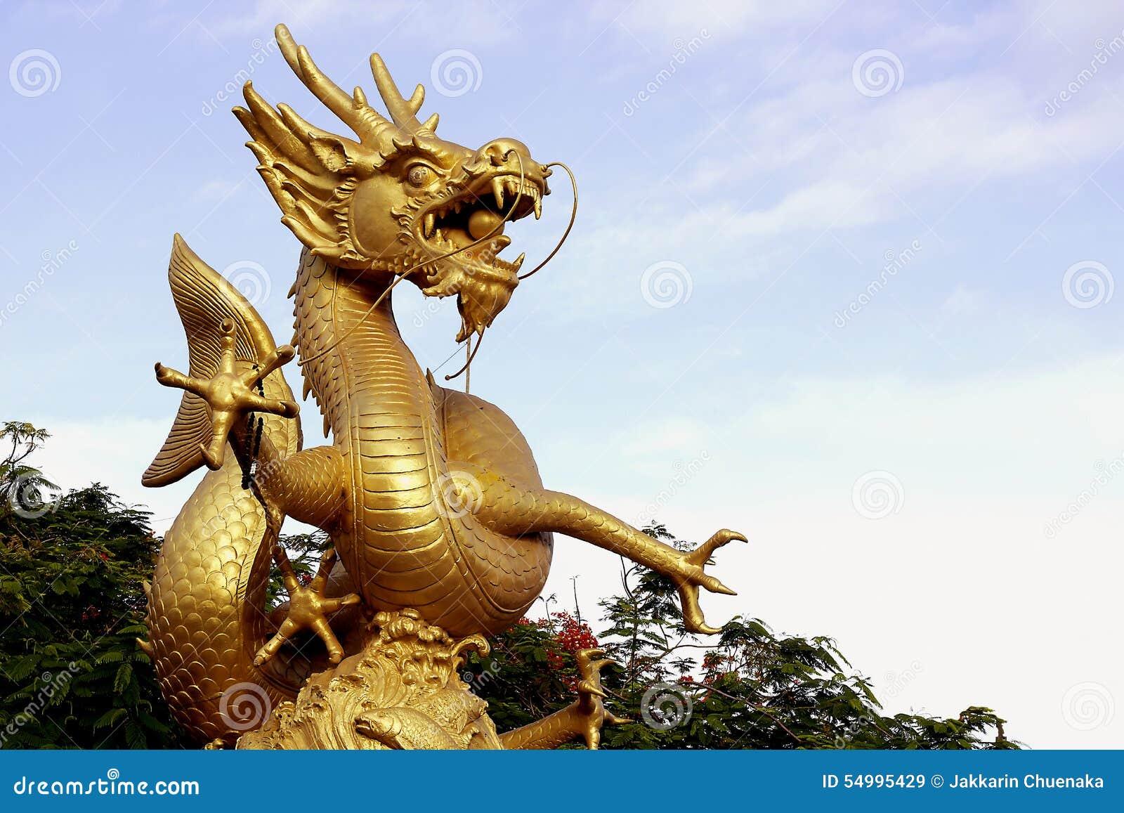 Guld- drakestaty med bakgrund för blå himmel