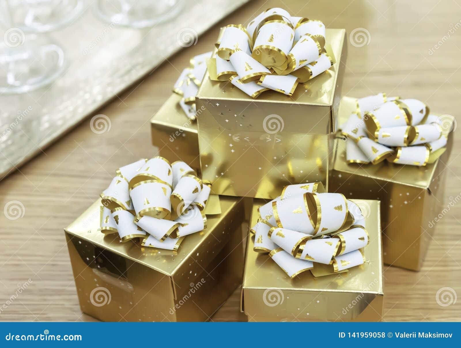 Guld- gåvaaskar med vita pilbågar på en trätabell