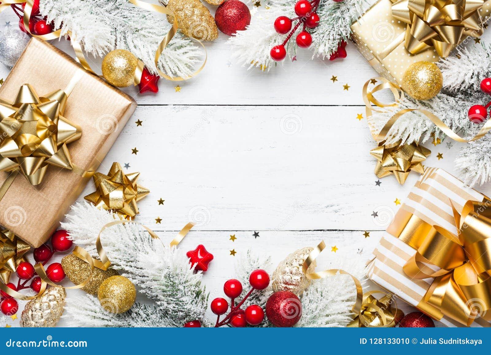 Guld- gåvor eller framlägger askar, det snöig granträdet och julgarneringar på den vita träbästa sikten för tabellen Lekmanna- lä