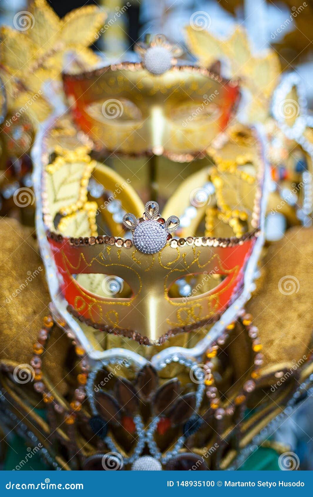 Guld- karnevalmaskering p? en nattkarneval i Indonesien