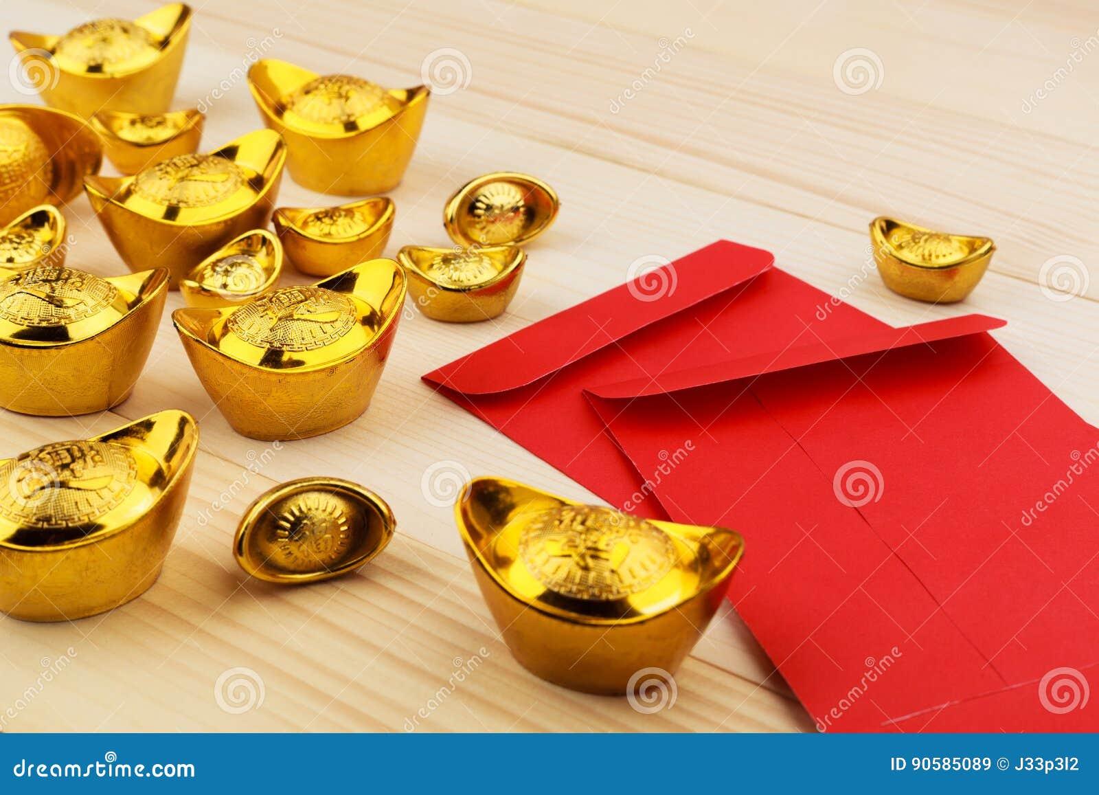 Guld- kinesisk tacka och tomma röda kuvert på träbakgrund