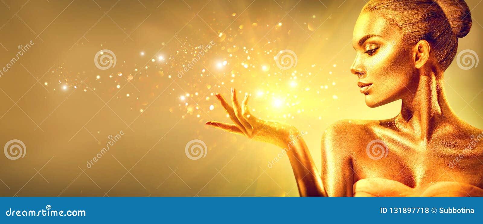 Guld- kvinna med den magiska gåvan för jul Flicka för skönhetmodemodell med guld- makeup, hår och smycken