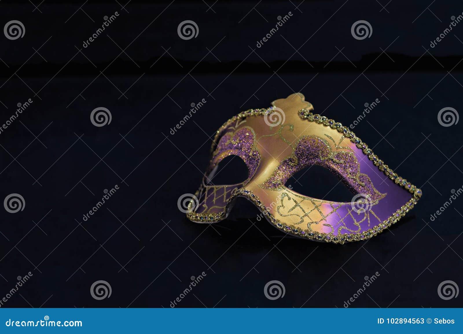 Guld- Mardi Gras eller karnevalmaskering som isoleras på en svart bakgrund