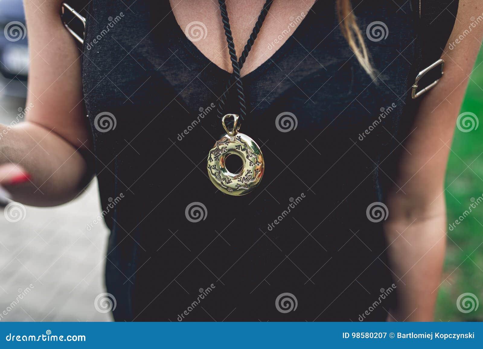 Guld- medaljong som hänger på hals för kvinna` s