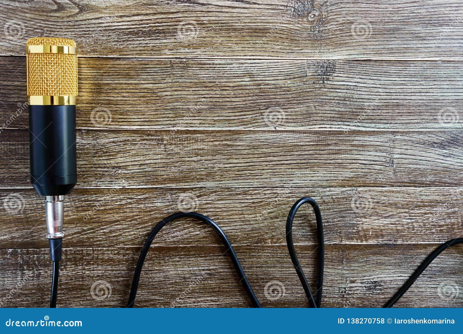 Guld- mikrofon för kondensator med kabellögner på en trätabell med kopieringsutrymme musikaliskt tema Lekmanna- lägenhet