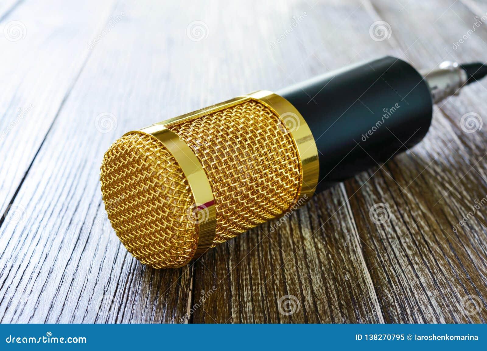 Guld- mikrofon för kondensator på en trätabell Ljuset från vänster sida