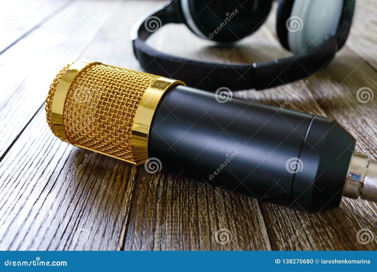 Guld- mikrofon- och hörlurarlögner för kondensator på en trätabell