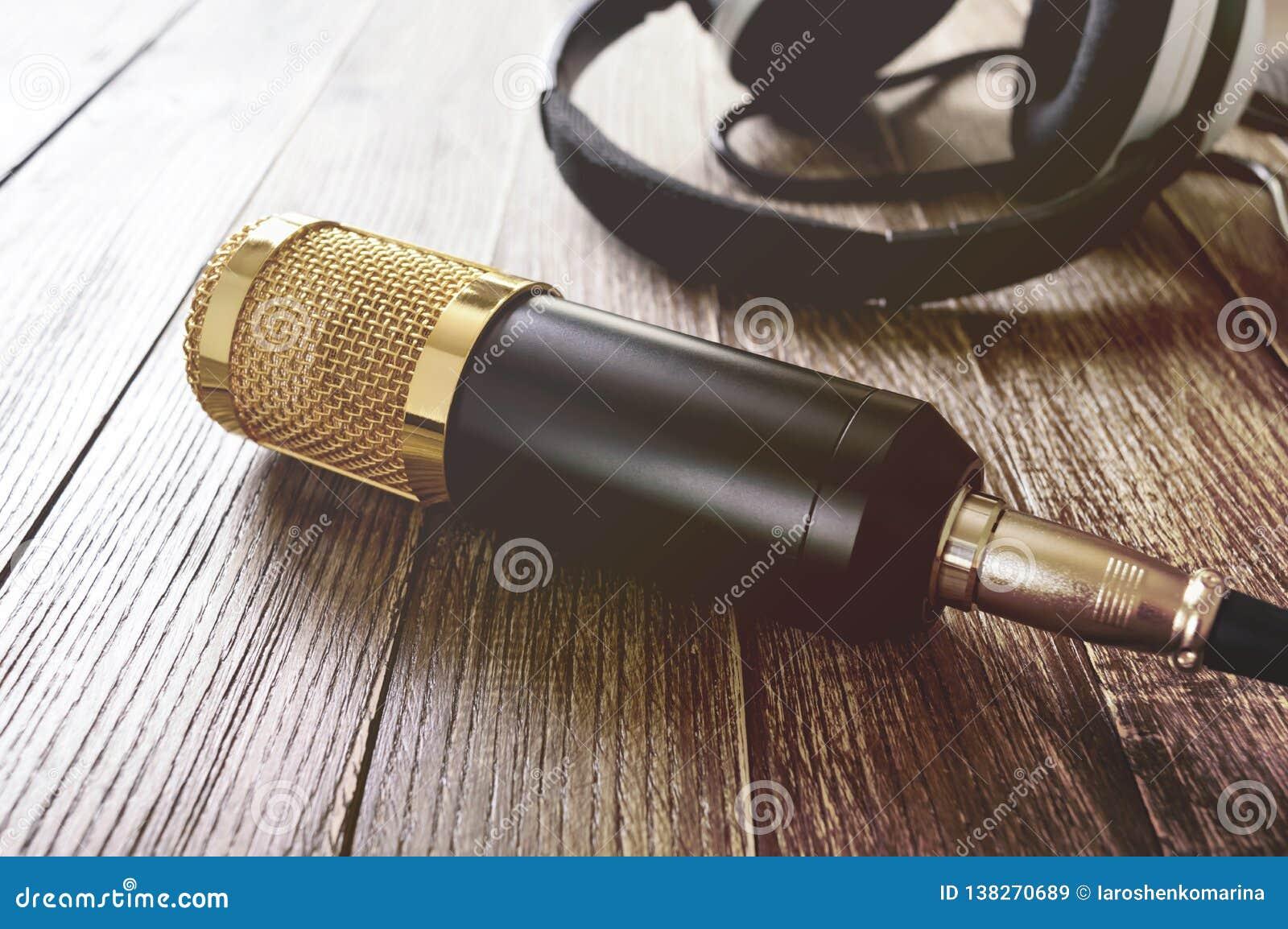 Guld- mikrofon- och hörlurarlögner för kondensator på en trätabell Ljuset från vänster sida
