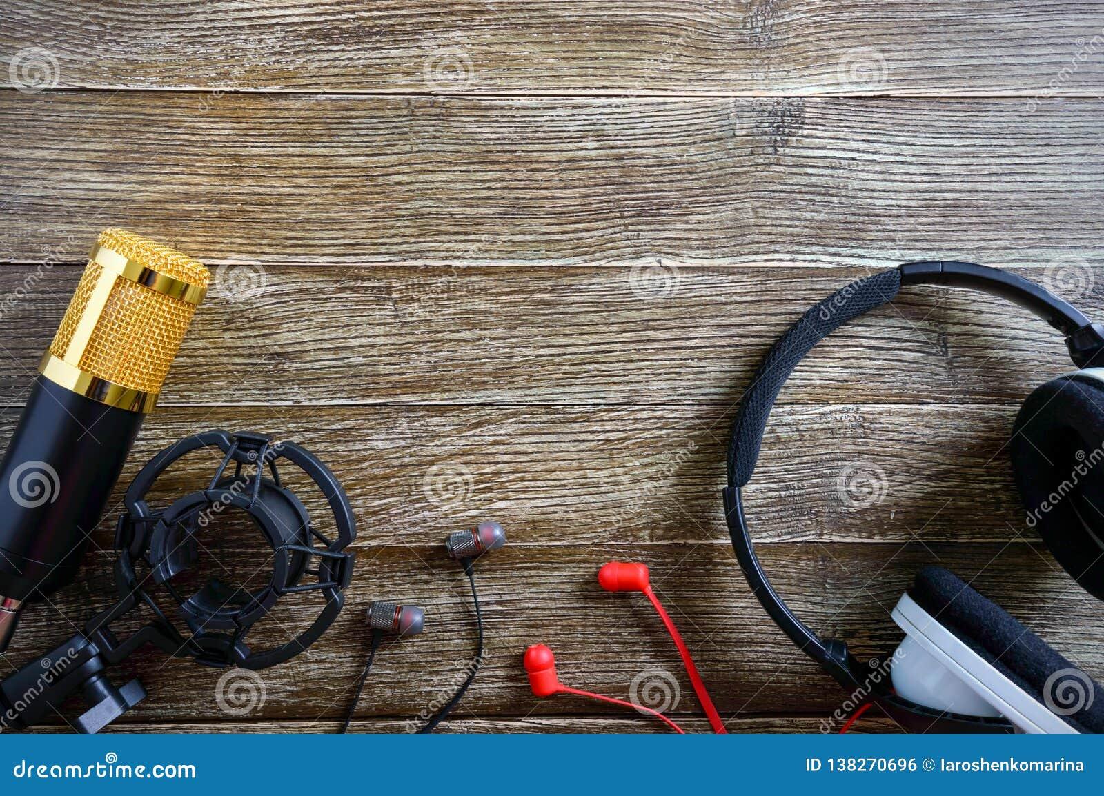 Guld- mikrofon- och hörlurarlögner för kondensator på en trätabell med kopieringsutrymme musikaliskt tema