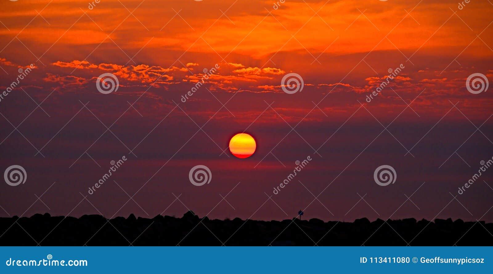 Guld- orange kust- soluppgångcloudscape