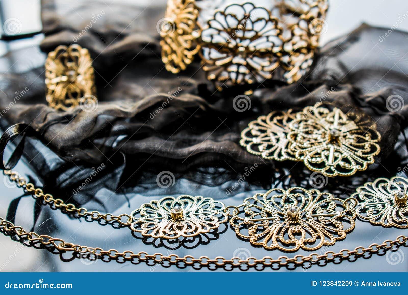 Guld- smycken är gula och olika skuggor Smycken från metalllegeringen med openwork modeller på den reflekterande yttersidan