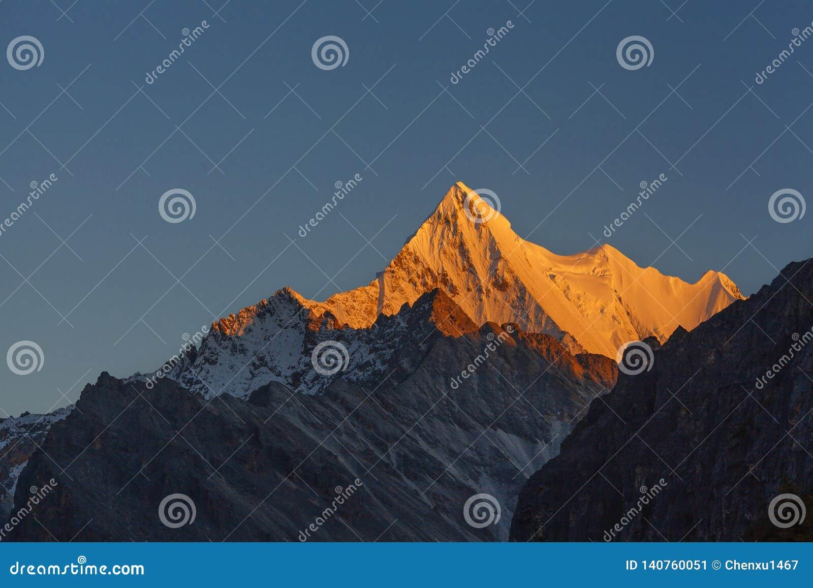 Guld- sol som skiner på berget Xianuoduoji