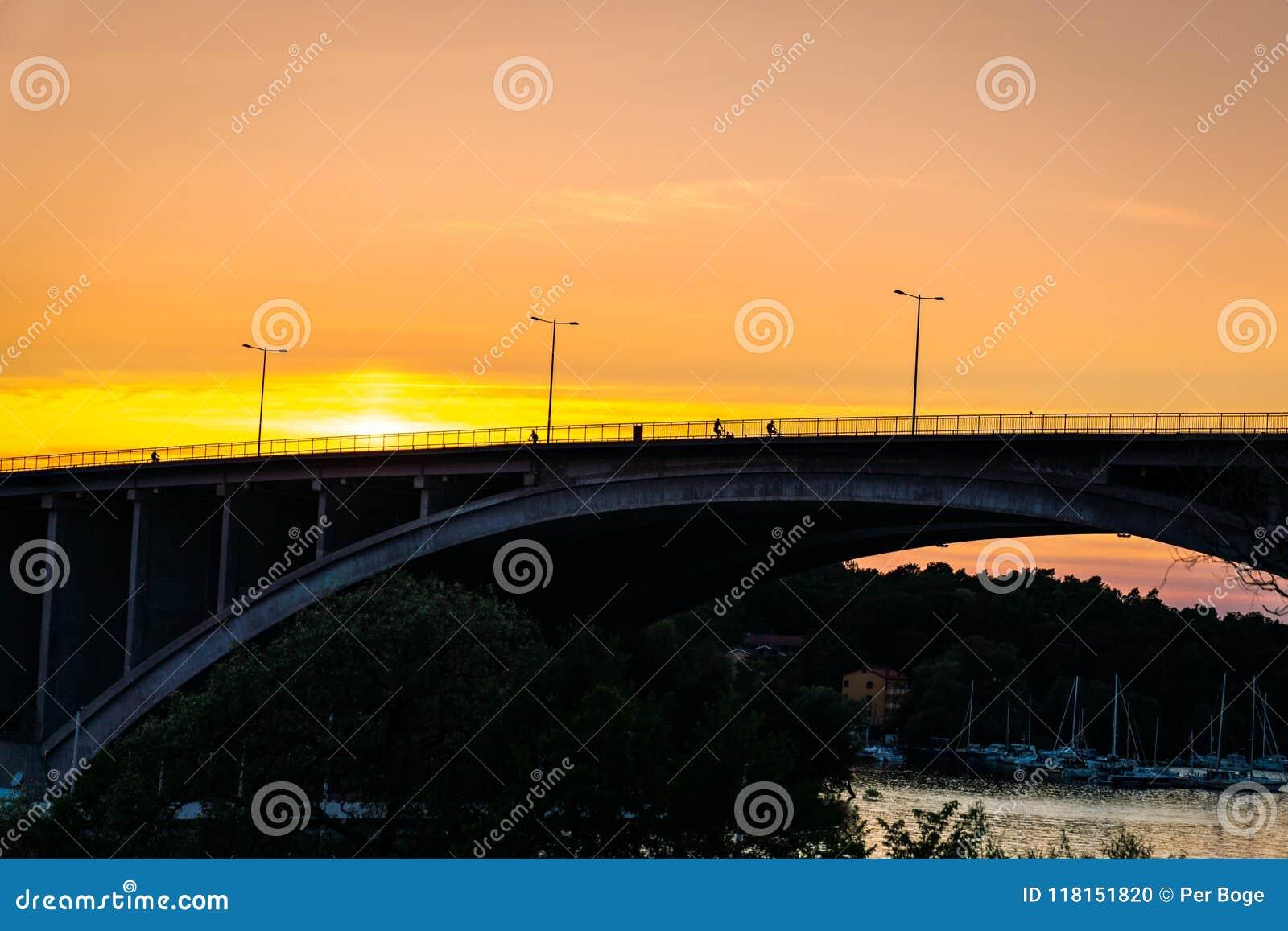 Guld- solnedgång med folk som cyklar på en bro