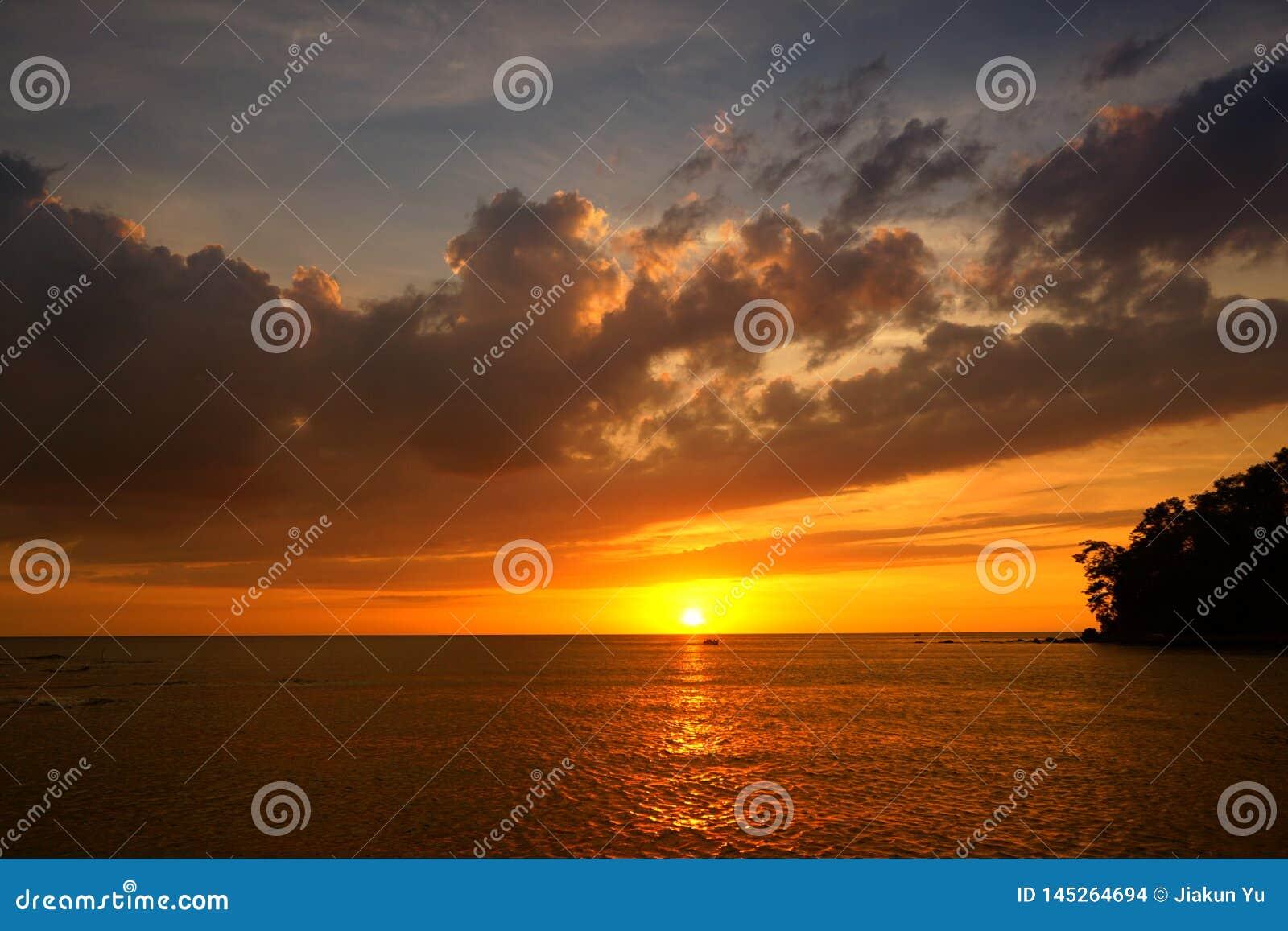 Guld- solnedgång på stranden med aftonglöd Havsreflexionsröda ljuset som soluppg