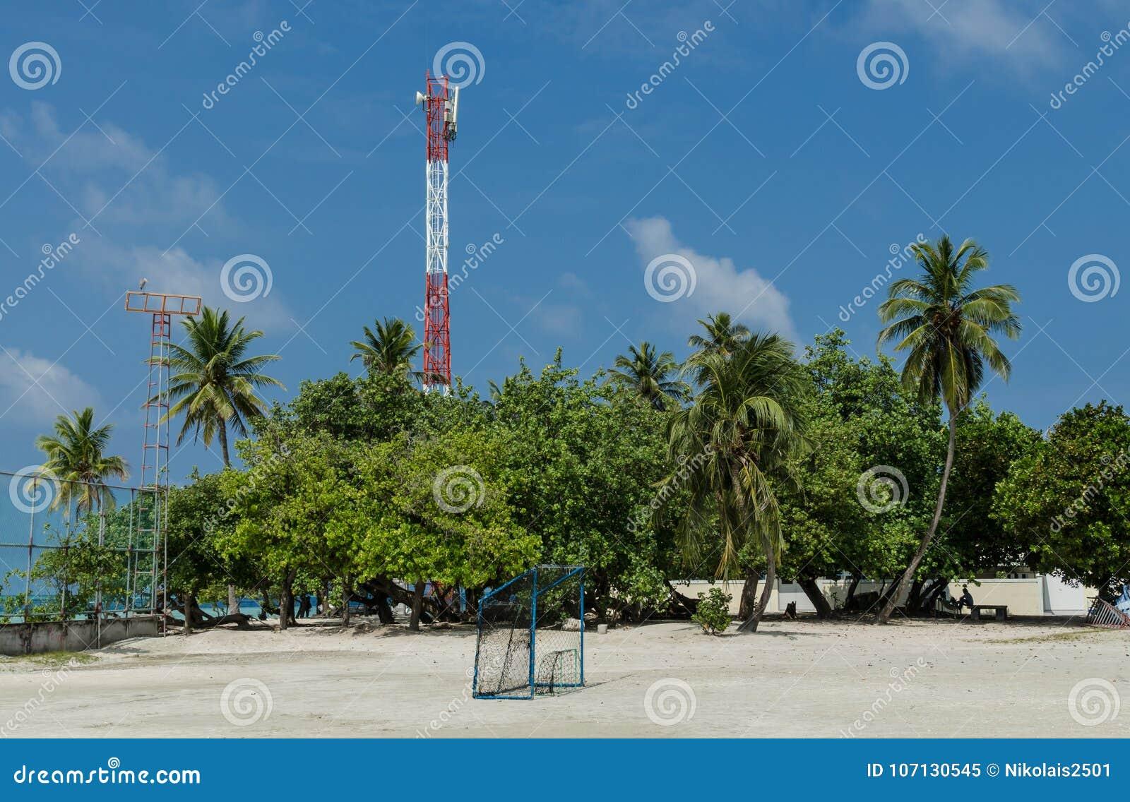 """GULHI-Insel, MALEDIVEN †""""im November 2017: Fußballplatz auf dem Hintergrund von Palmen und Telekommunikation ragt hoch"""