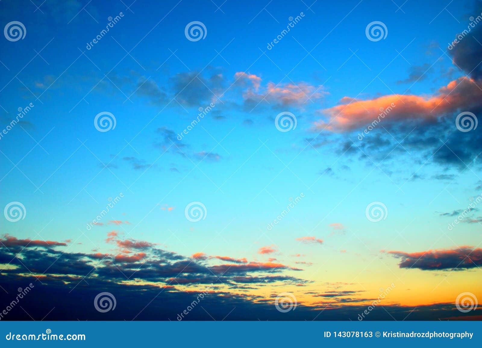 Guling-blått himmel med ljusa moln