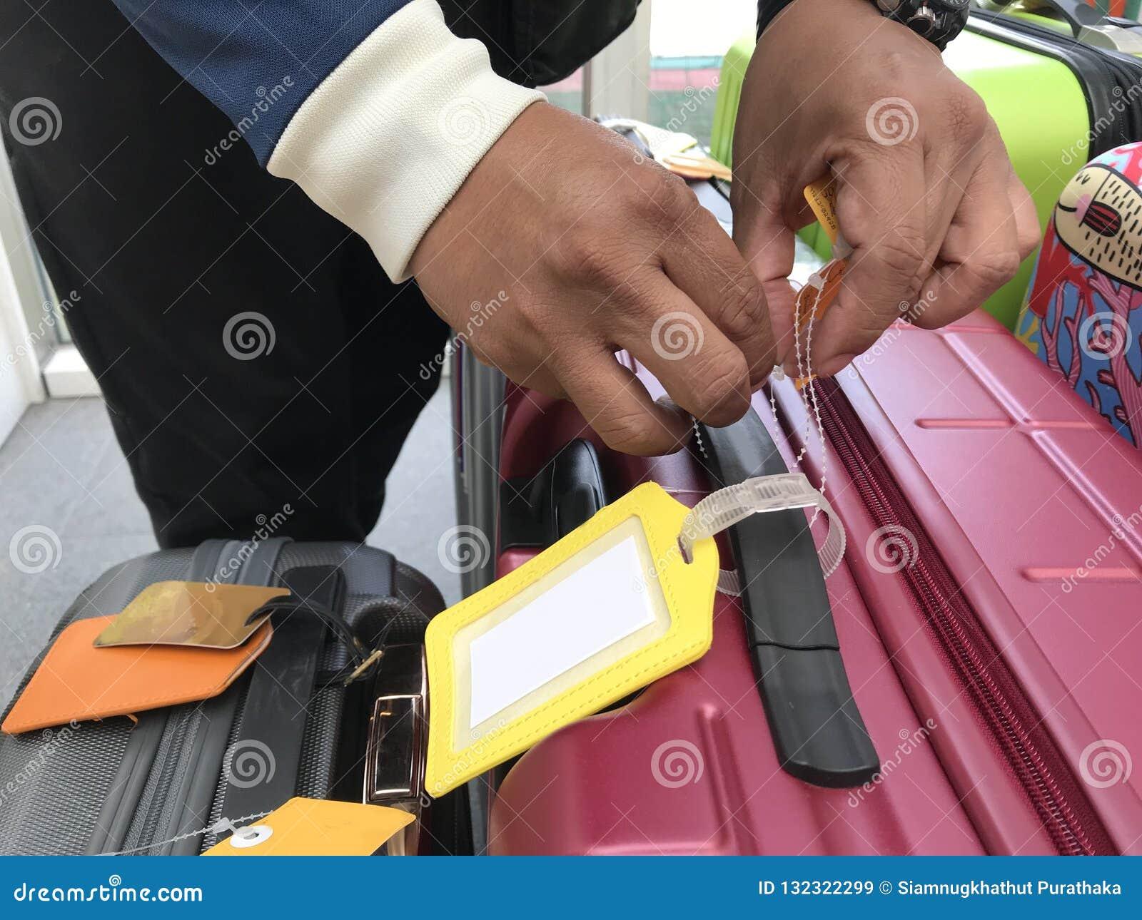 Guling piskar etiketten på en röd resväska