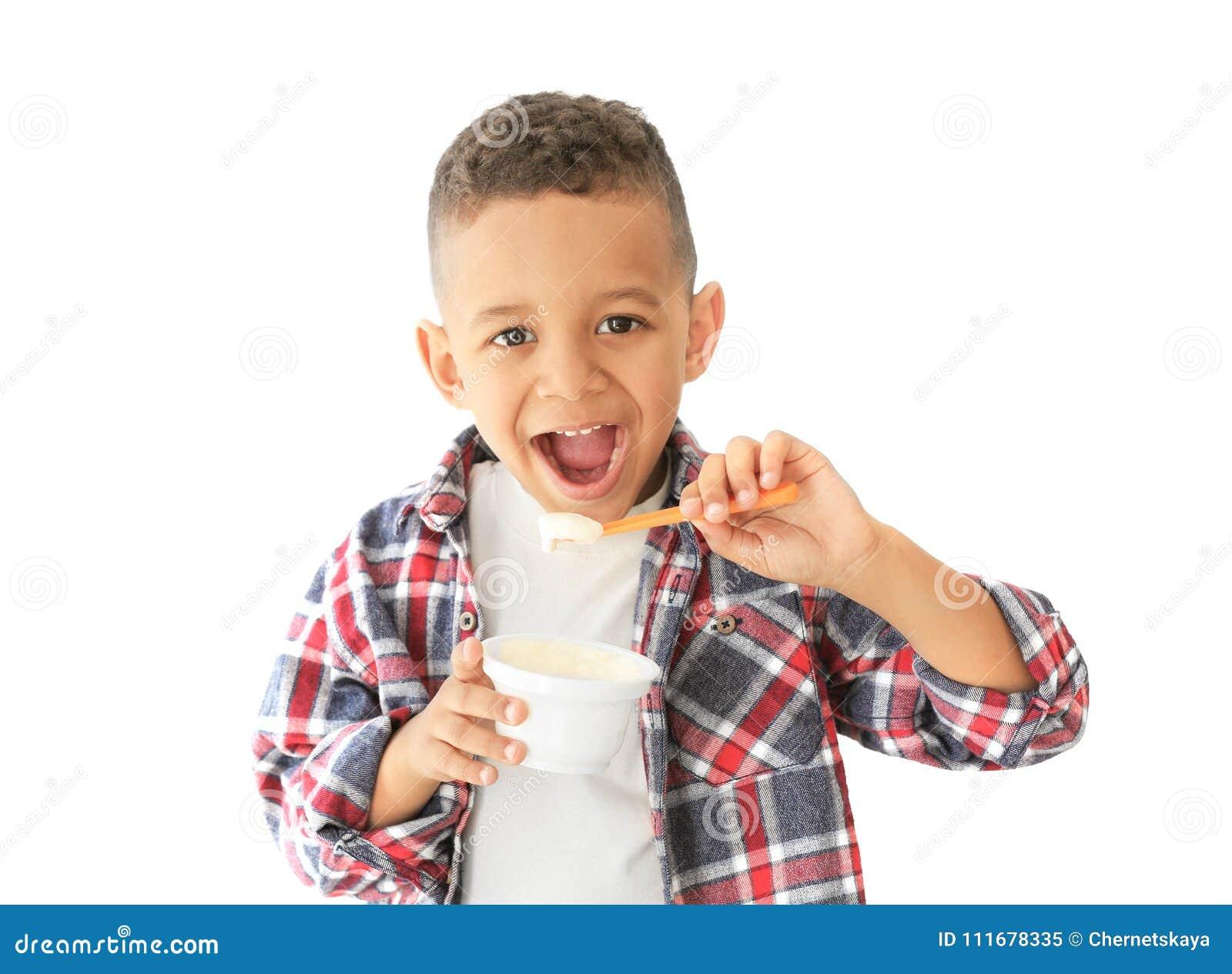 Gullig afrikansk amerikanpojke som äter yoghurt