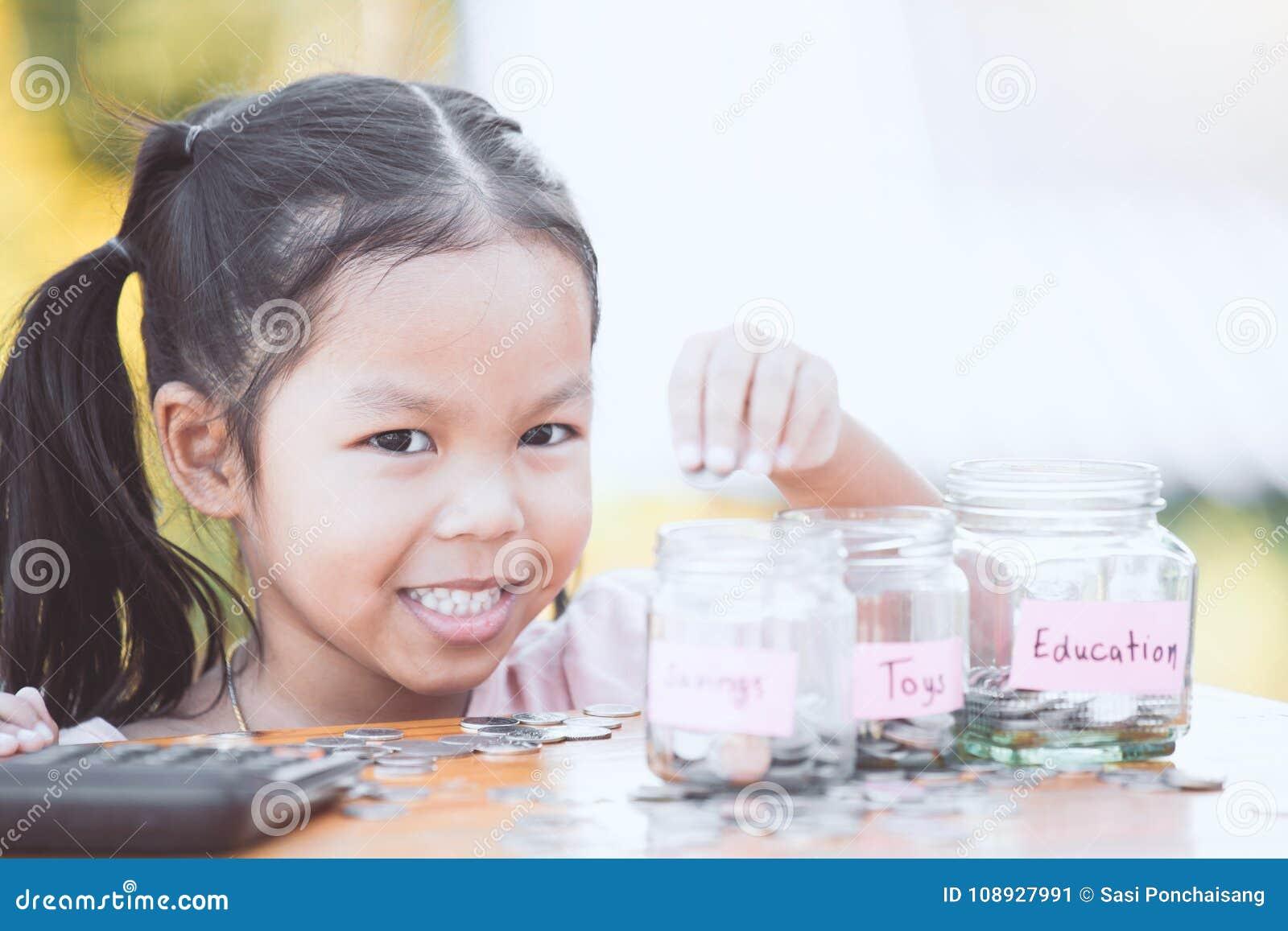 Gullig asiatisk flicka för litet barn som sätter myntet in i glasflaskan
