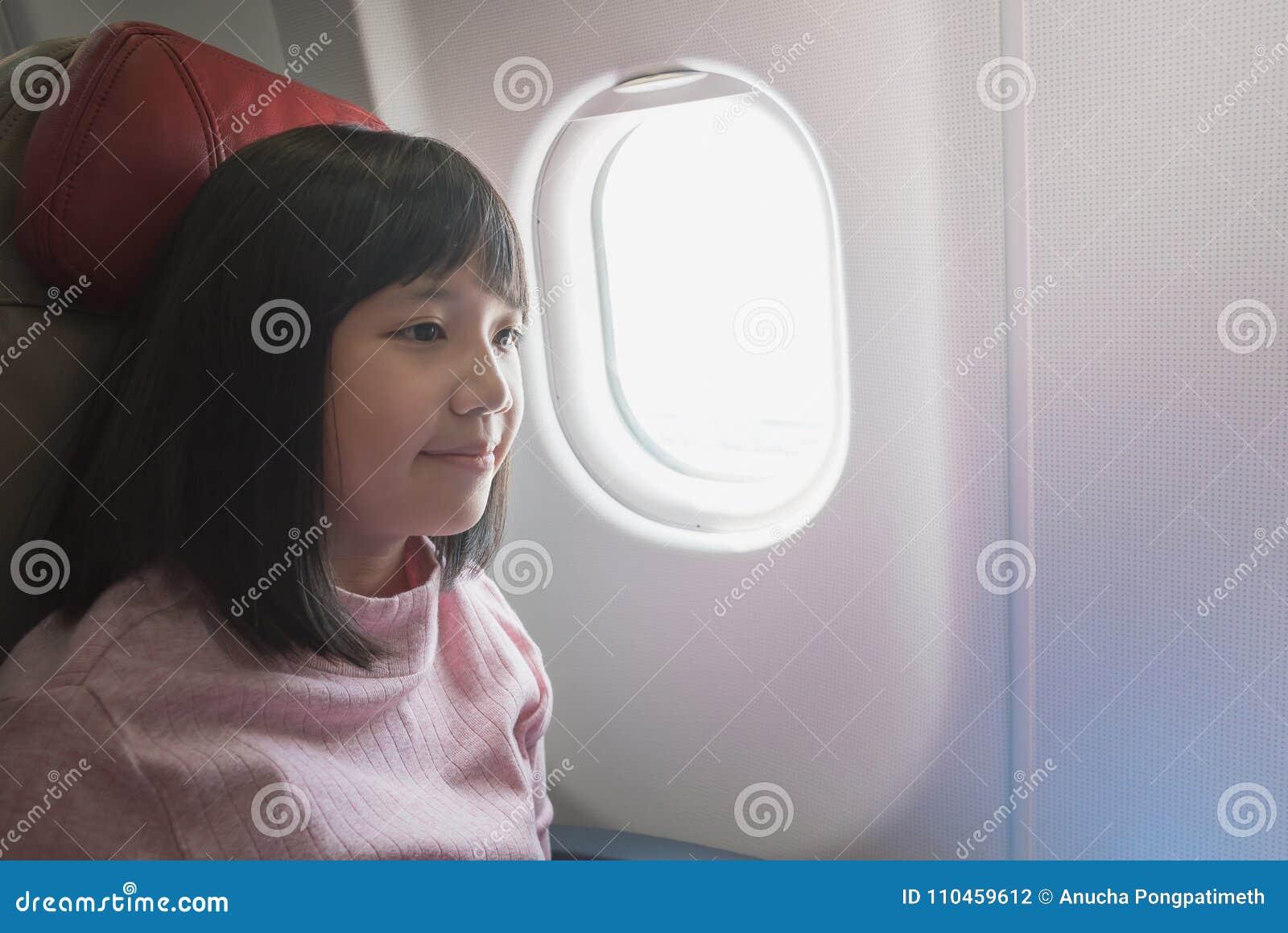 Gullig asiatisk flicka på flygplanet