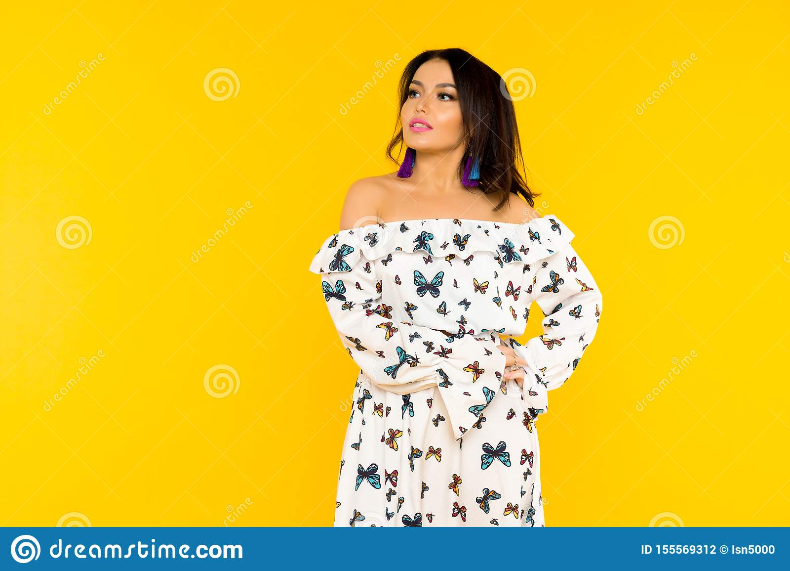 Gullig asiatisk kvinna i siden- klänning med fjärilar som poserar på gul bakgrund
