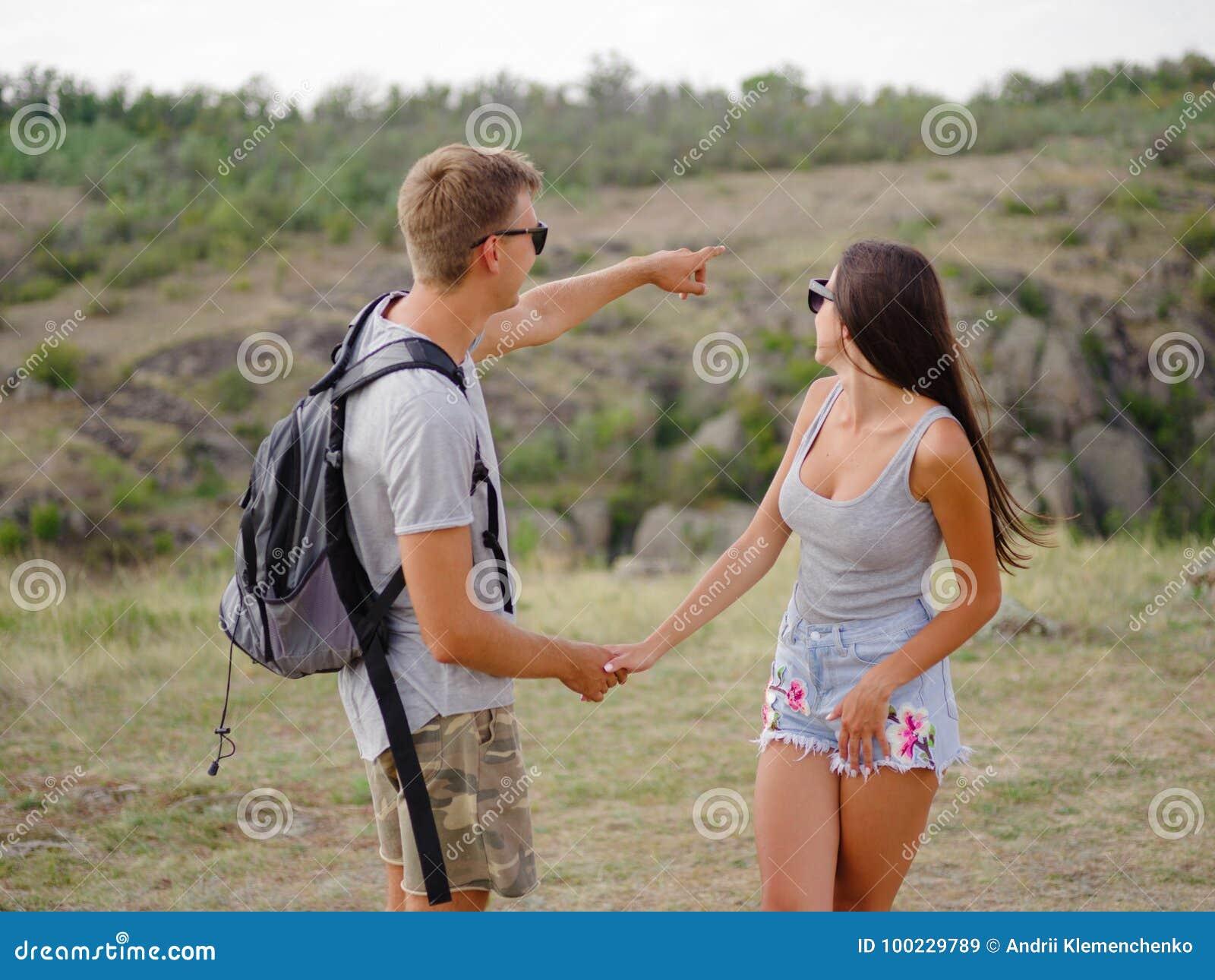 Gullig attraktiv flickvän och stark positiv pojkvän på en naturlig bakgrund Unga fotvandrare Romantiker snubblar begrepp