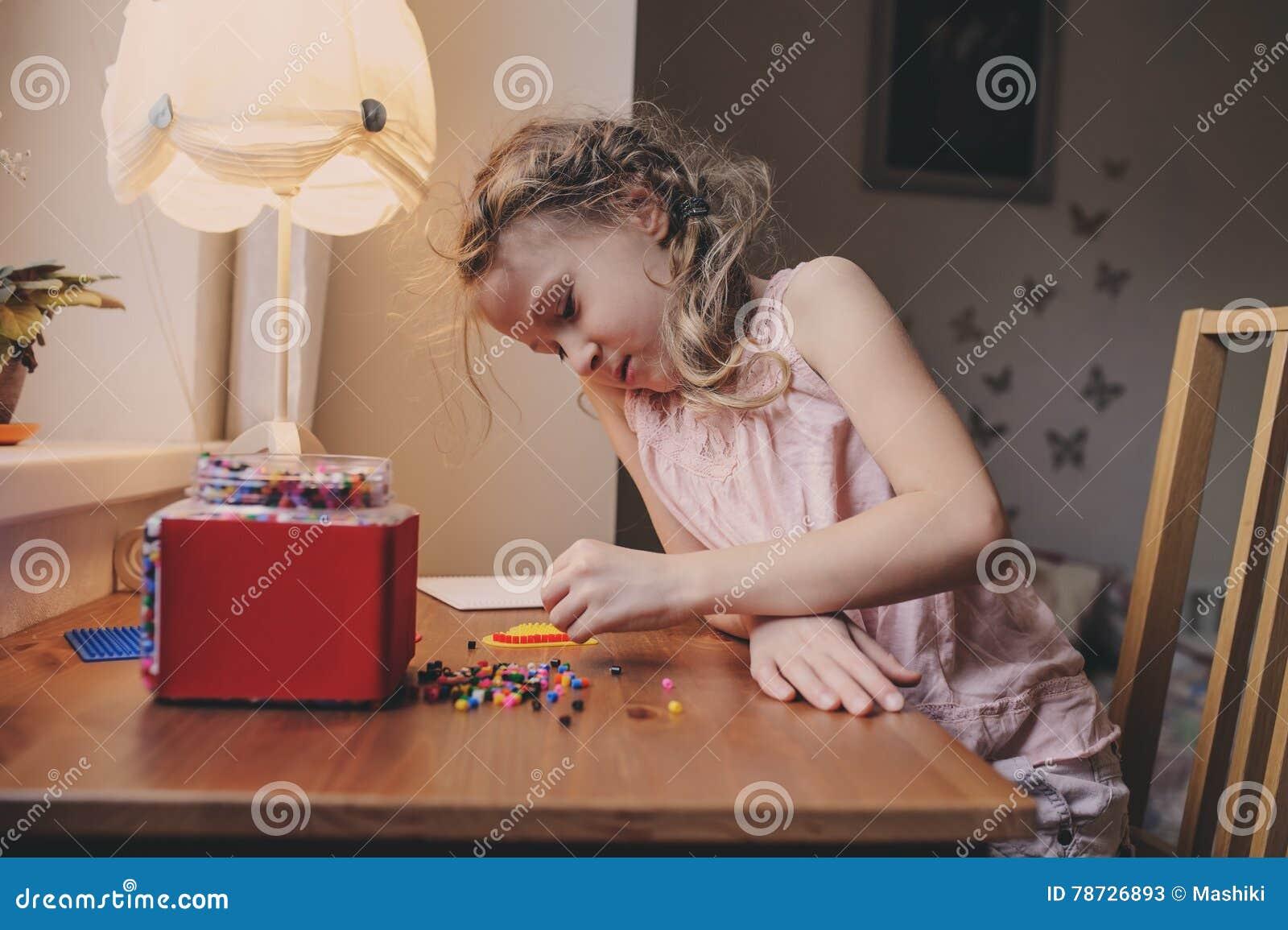 Gullig barnflicka som spelar med mosaiken som är hemmastadd i hennes rum