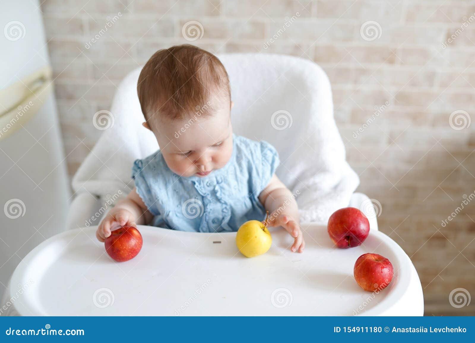 Gullig förtjusande Caucasian barnungeflicka som sitter i hög stol som äter äpplefrukt Daglig livsstil Verkligt autentiskt sött he