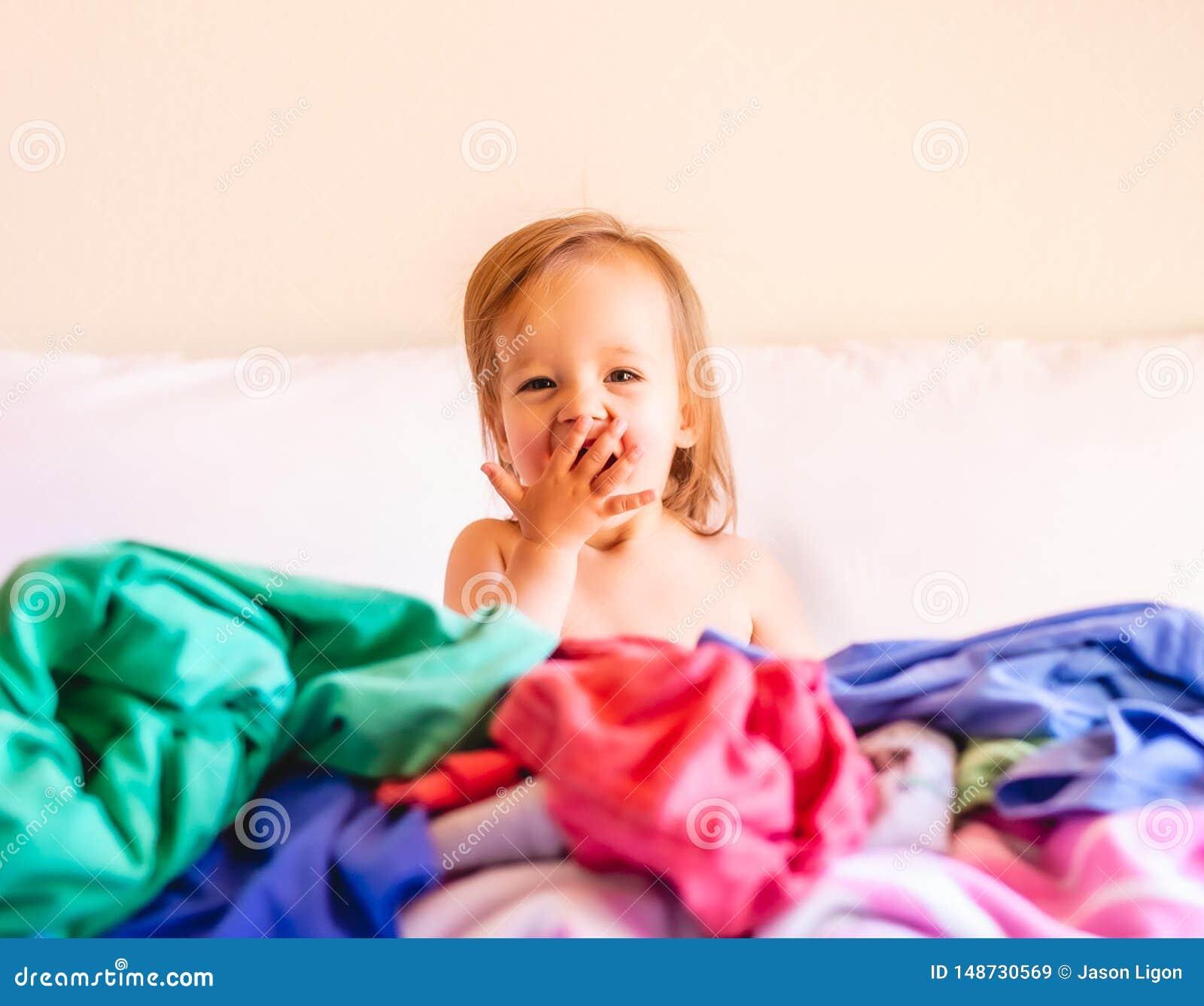 Gullig f?rtjusande och att le, behandla som ett barn caucasianen att sitta i en h?g av den smutsiga tv?tterit p? s?ng