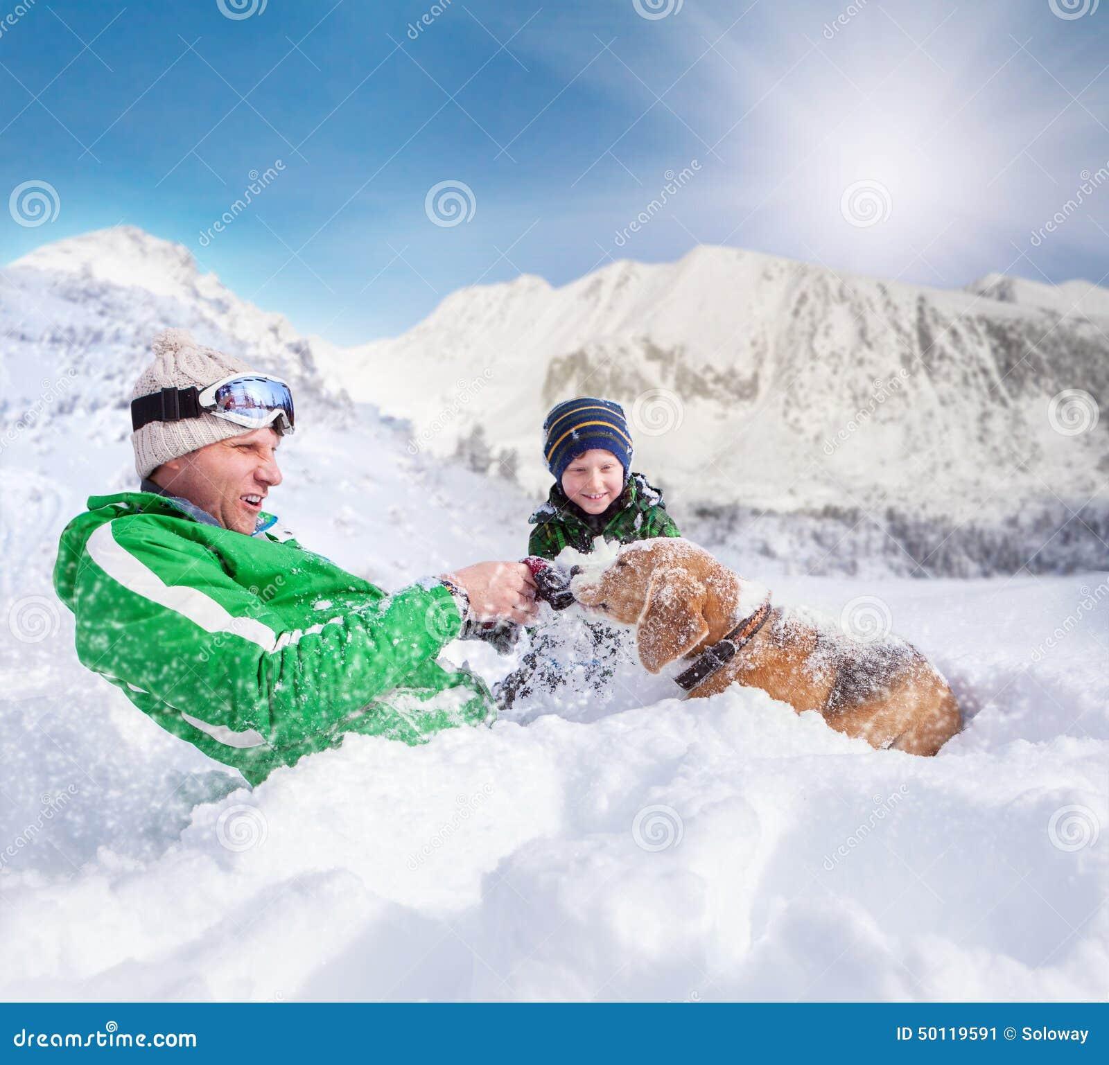 Gullig familjplats: fadern och sonen spelar med hunden under berget