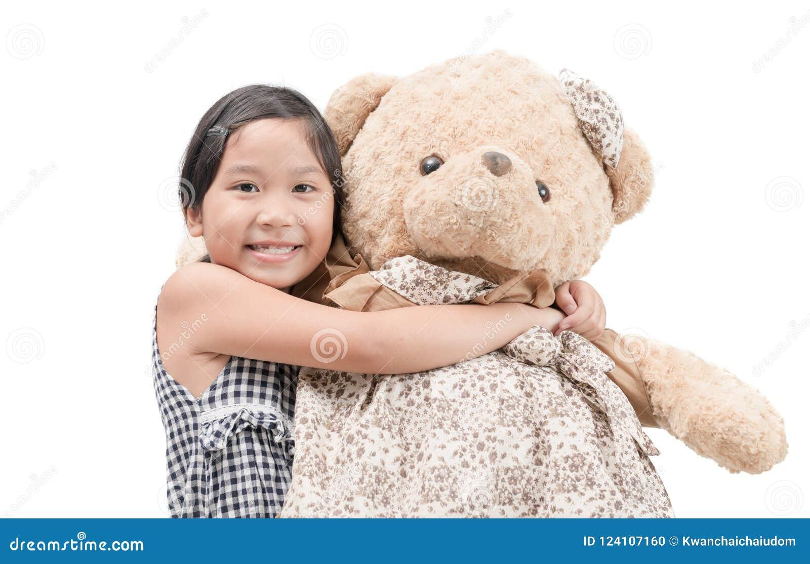 Gullig flicka som kramar stora den isolerade nallebjörnen