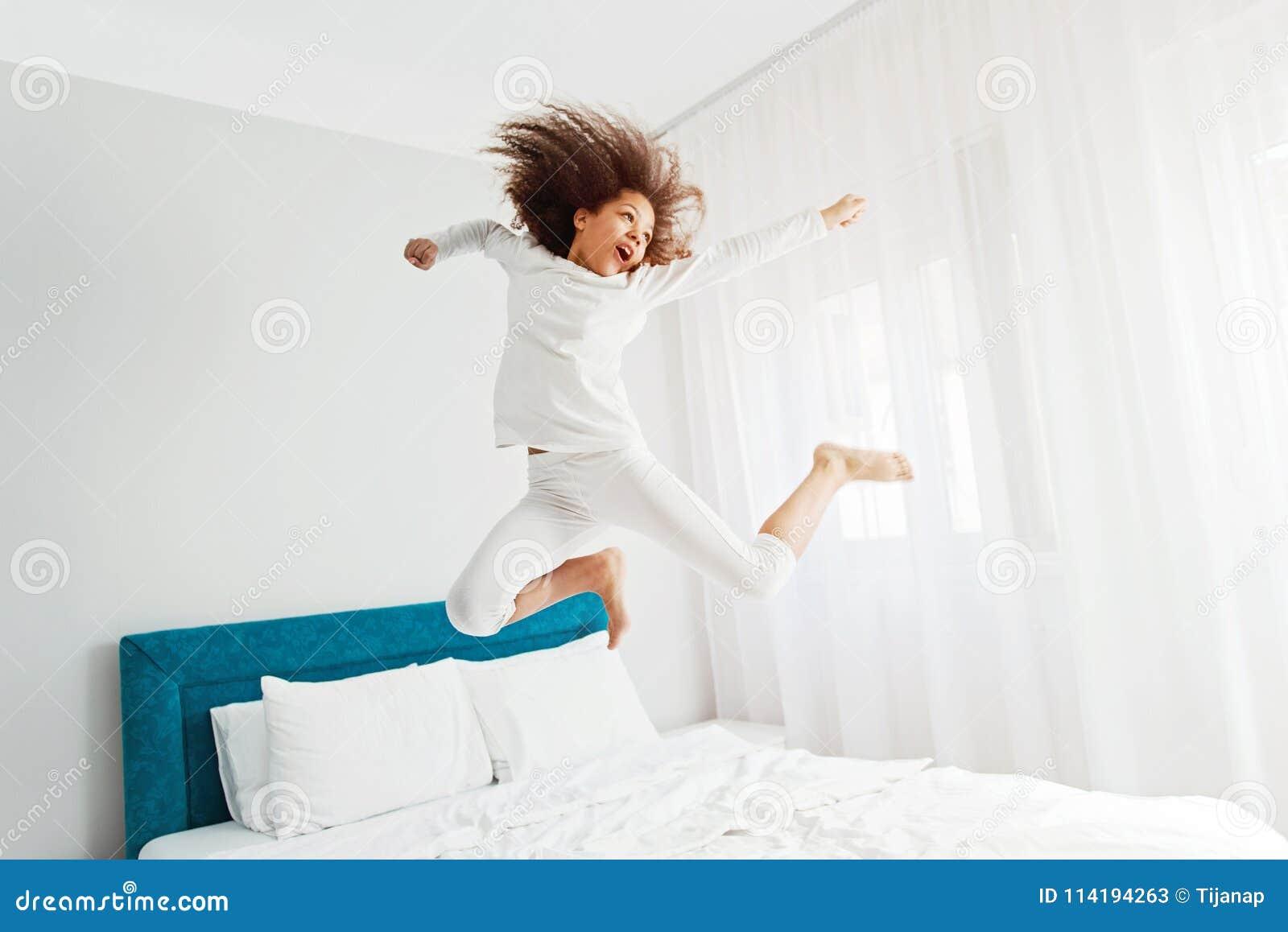 Gullig flickabanhoppning på sängen, lycka