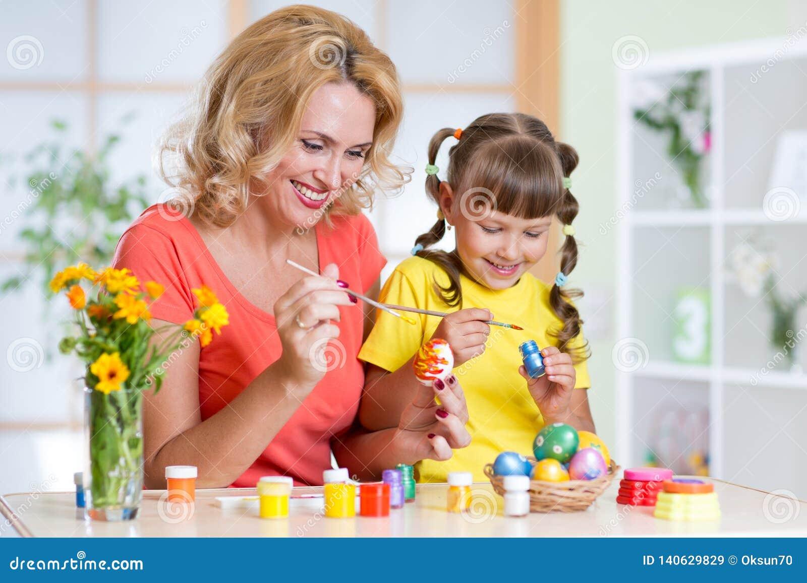 Gullig kvinna- och ungeflicka som hemma dekorerar påskägg