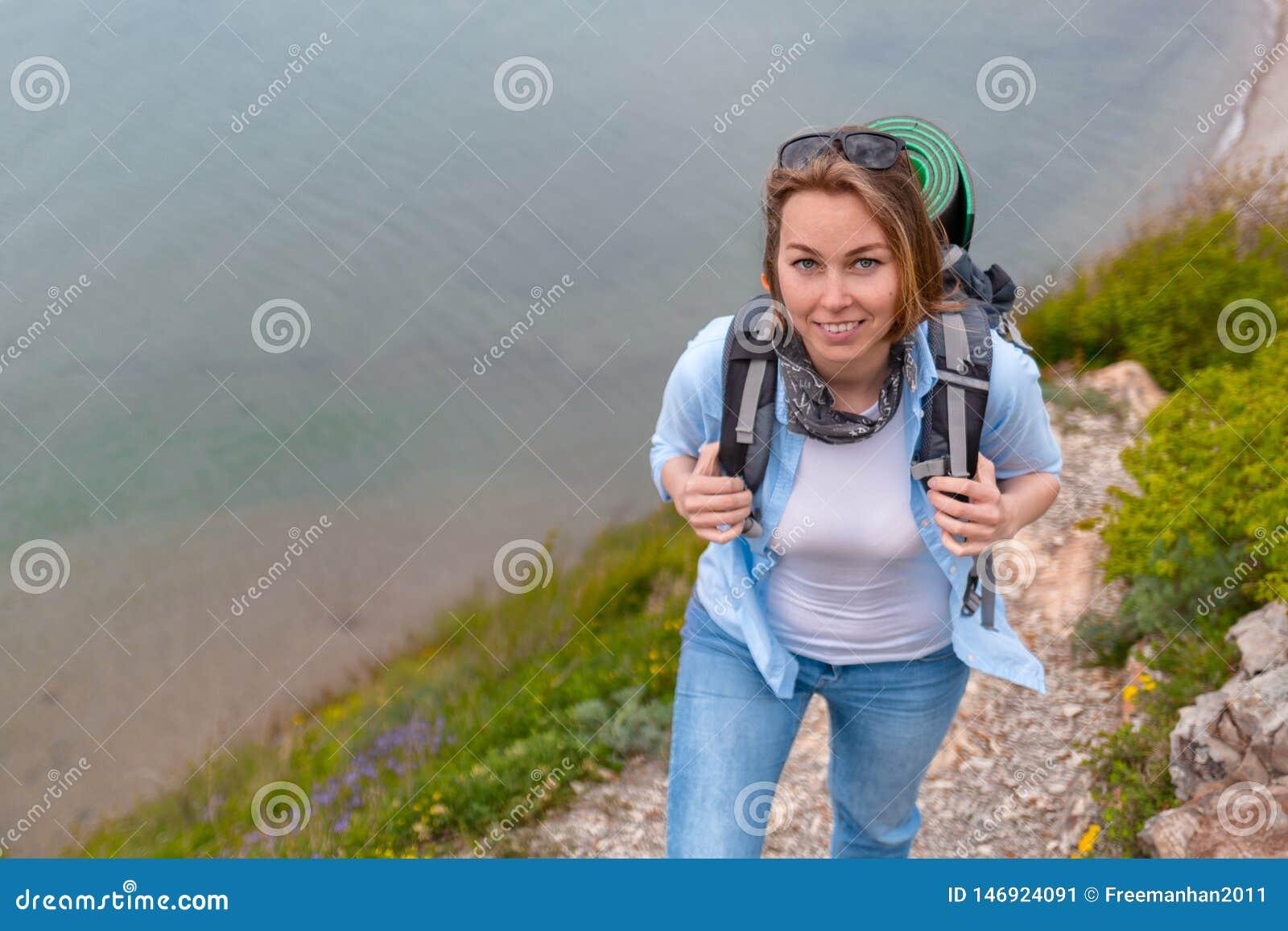 Gullig kvinnaturist som promenerar en bergslinga Fotvandra och sportar close upp