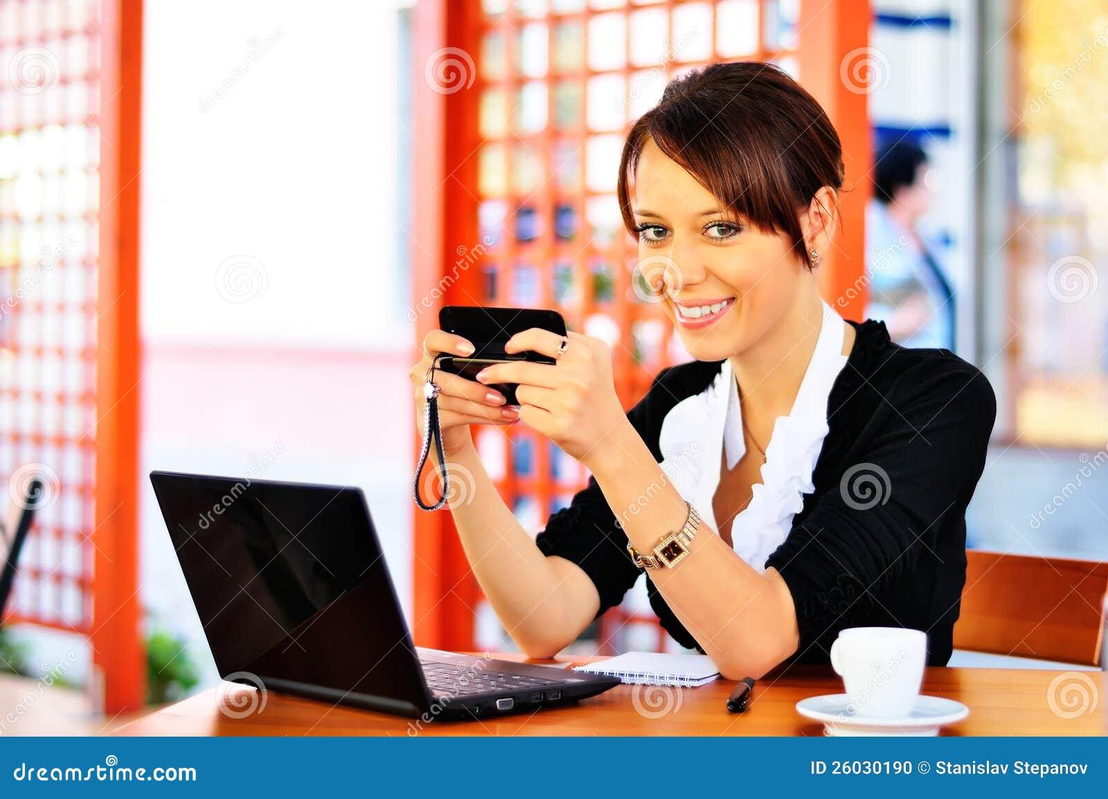 Gullig kvinnlig på cafen genom att använda mobiltelefon och bärbar dator