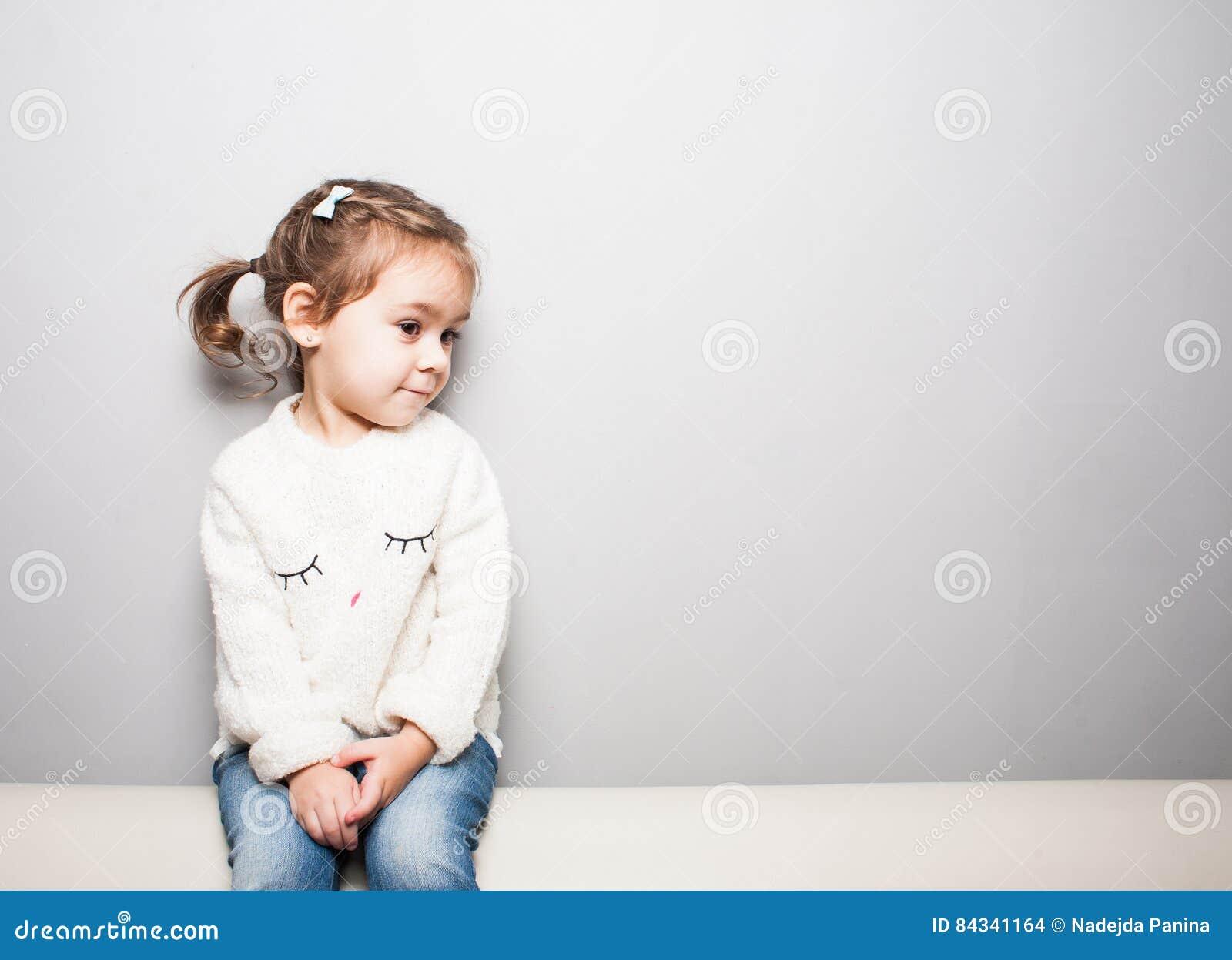 Gullig le liten flicka på grå bakgrund