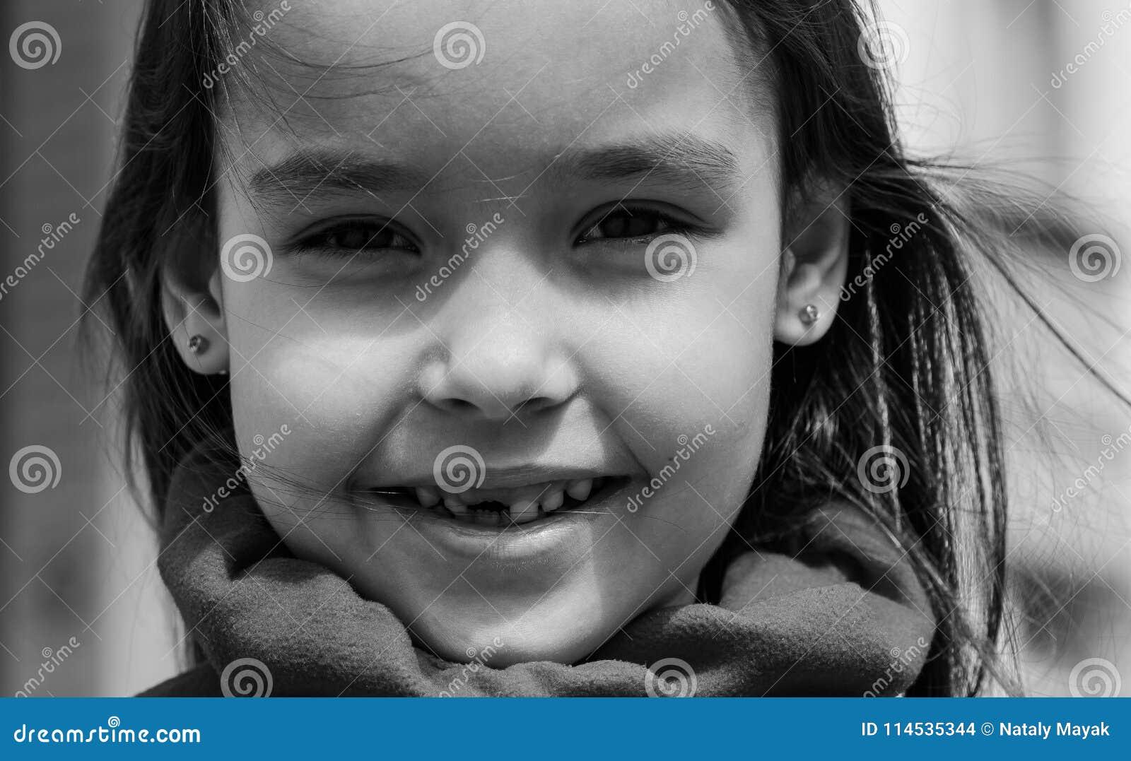 Gullig le tandlös flicka som ser kameran i svartvit bild