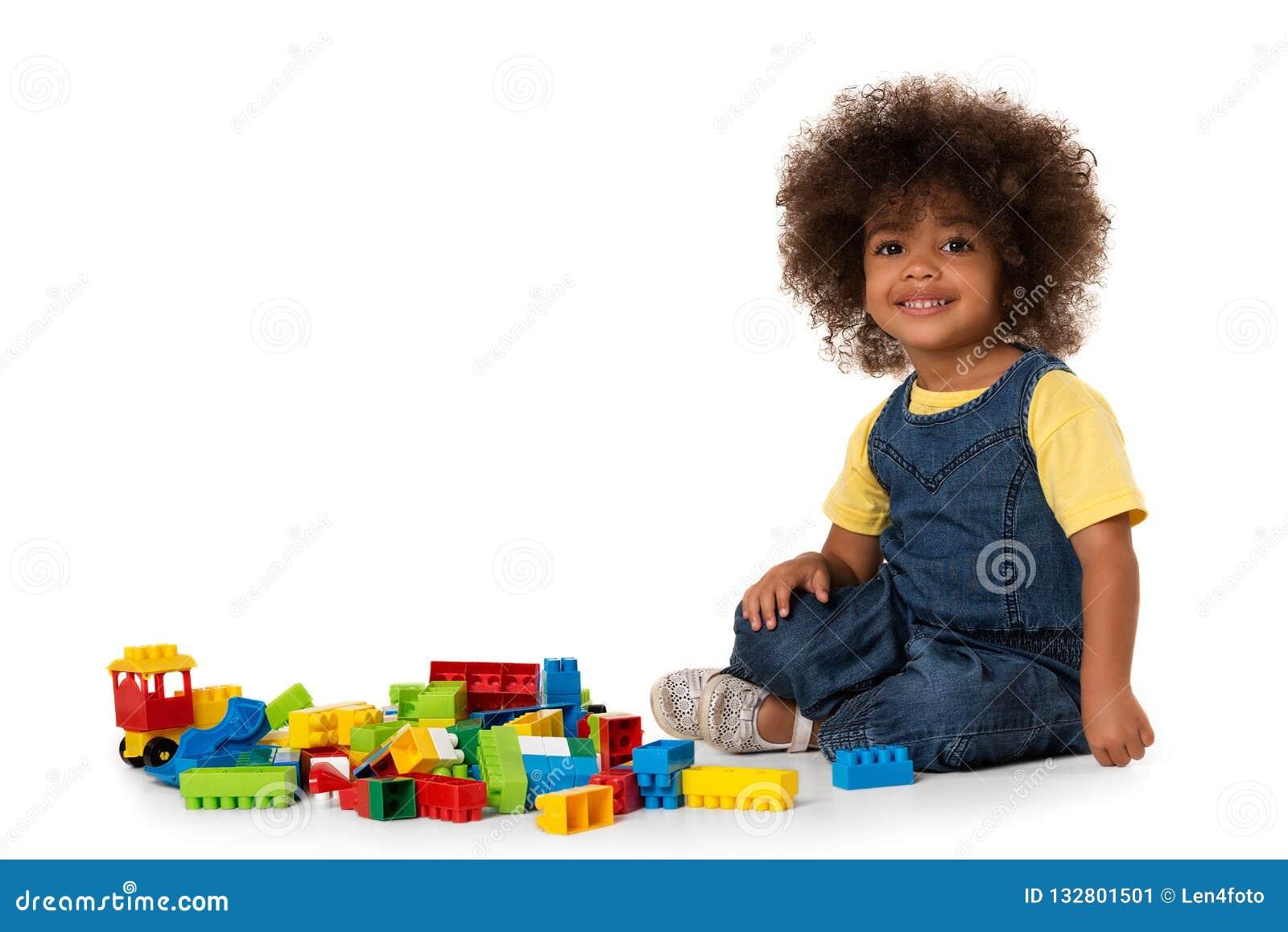 Gullig liten afrikansk amerikanflicka som spelar med massor av färgrika plast- kvarter inomhus isolerat