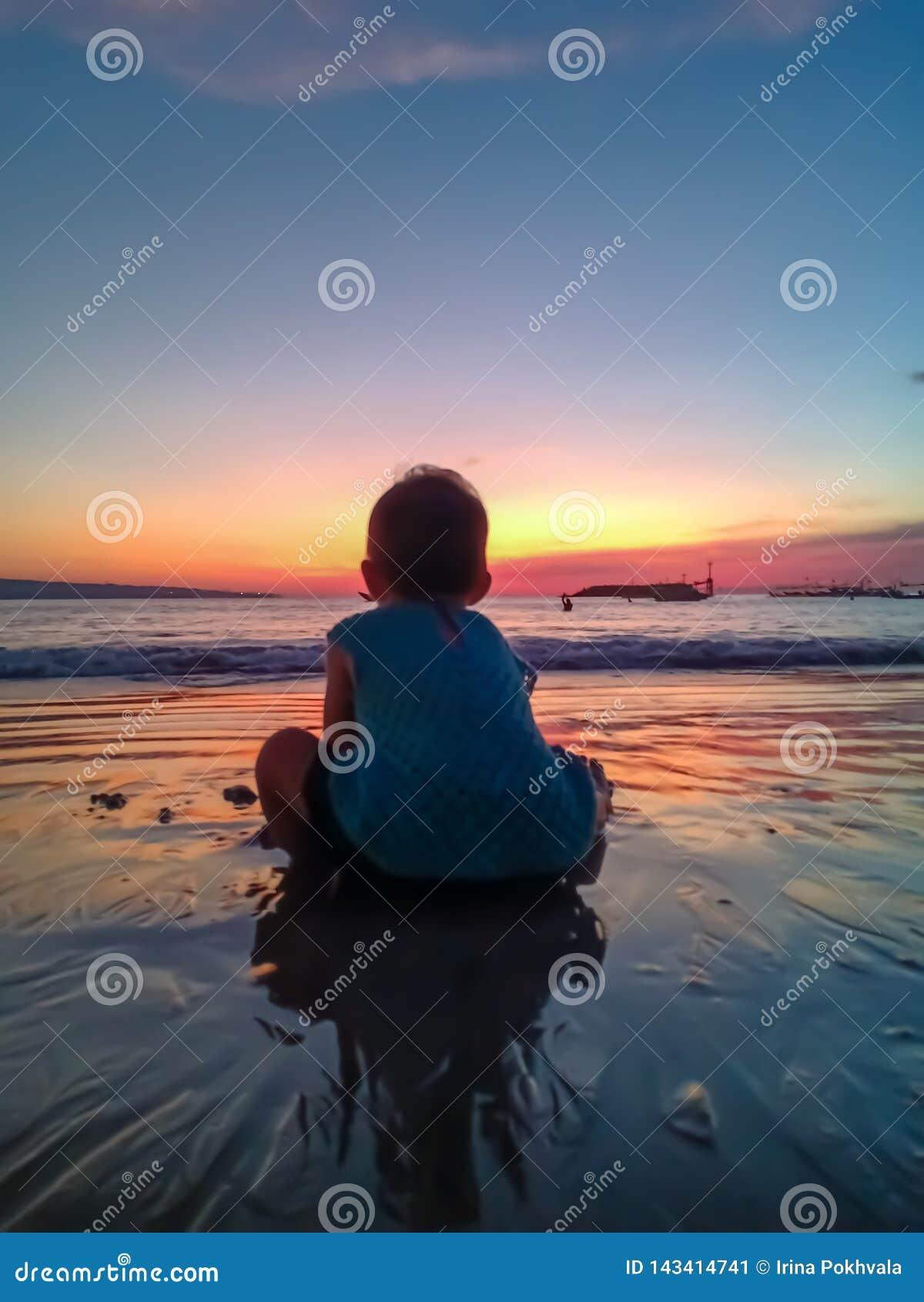 Gullig liten flicka att möta solnedgången och hagyckeln på stranden