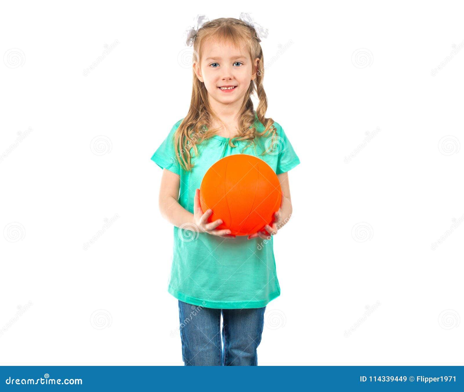 Gullig liten flicka med en boll som ser in i kameran och le