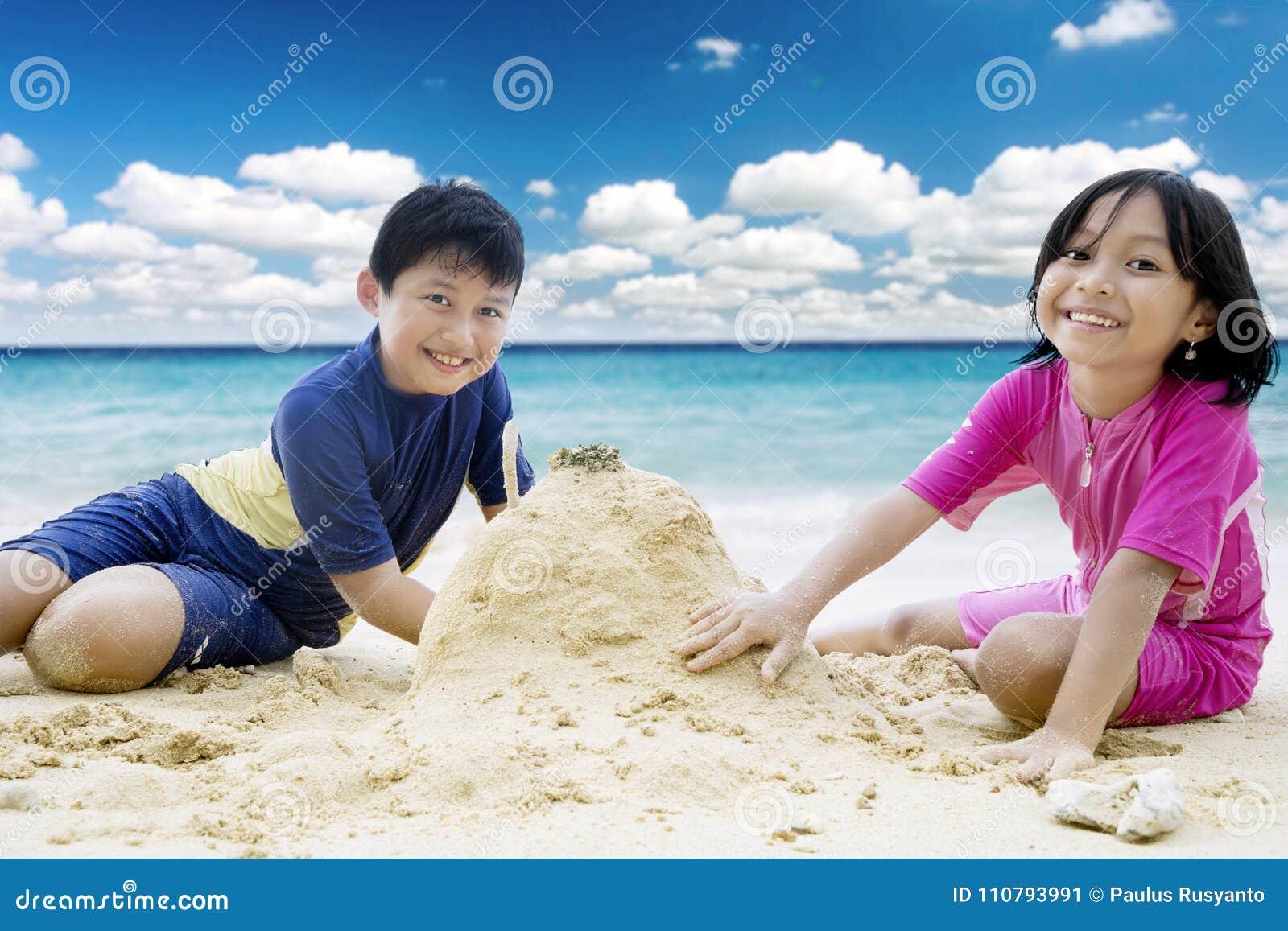 Gullig liten flicka med hennes broder som spelar sand