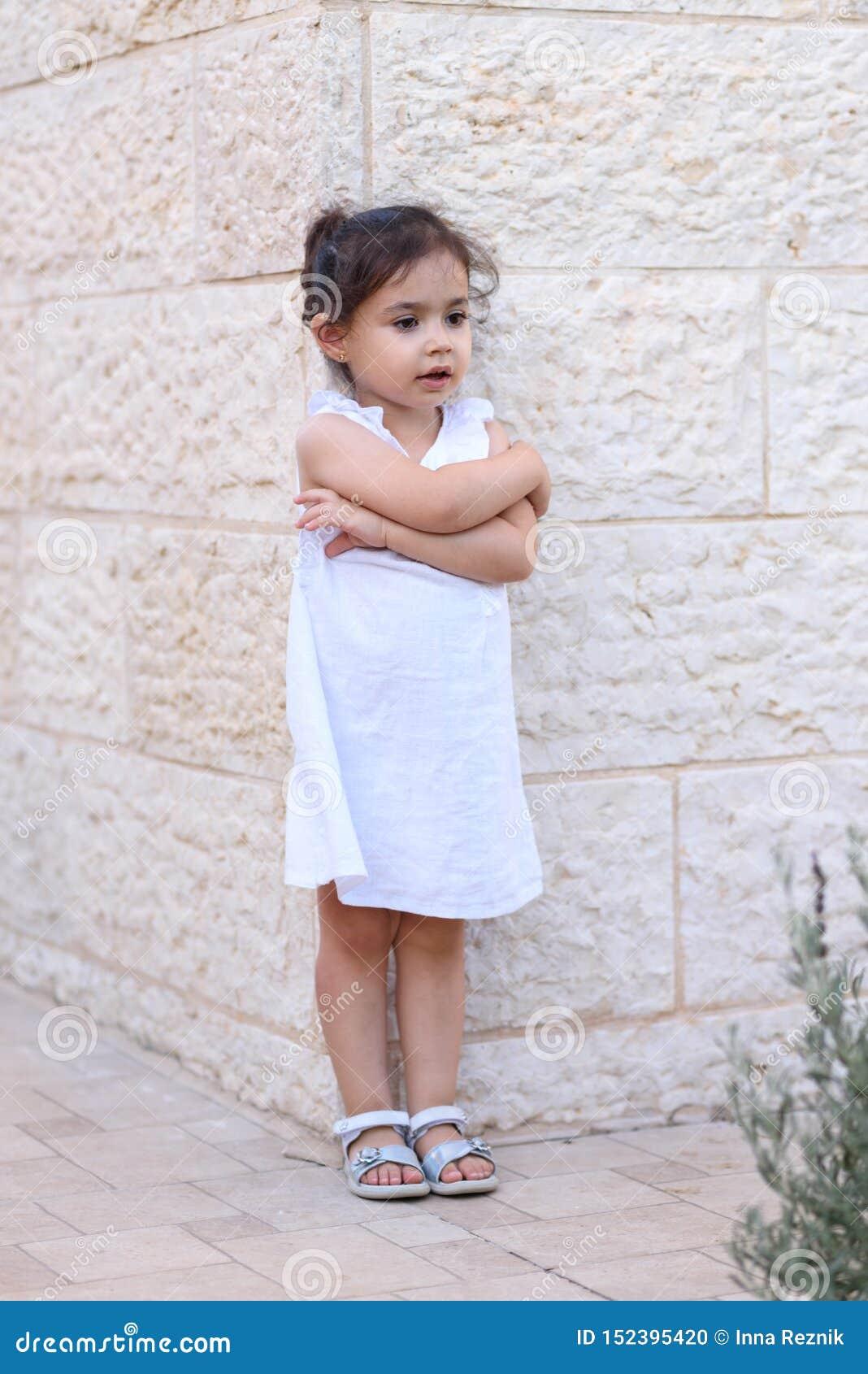 Gullig liten flicka med vitt posera för klänning som är utomhus- field treen