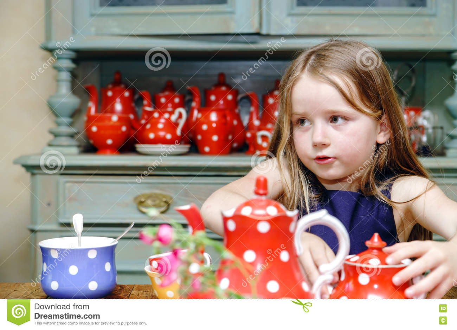 Gullig liten flicka som förbereder te i tekanna