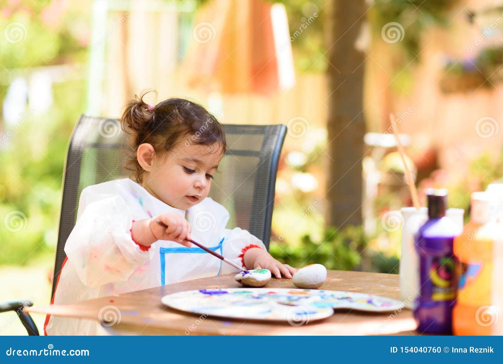 Gullig liten flicka som har roligt och att färga med borsten, handstil och att måla på sommar eller höstträdgården