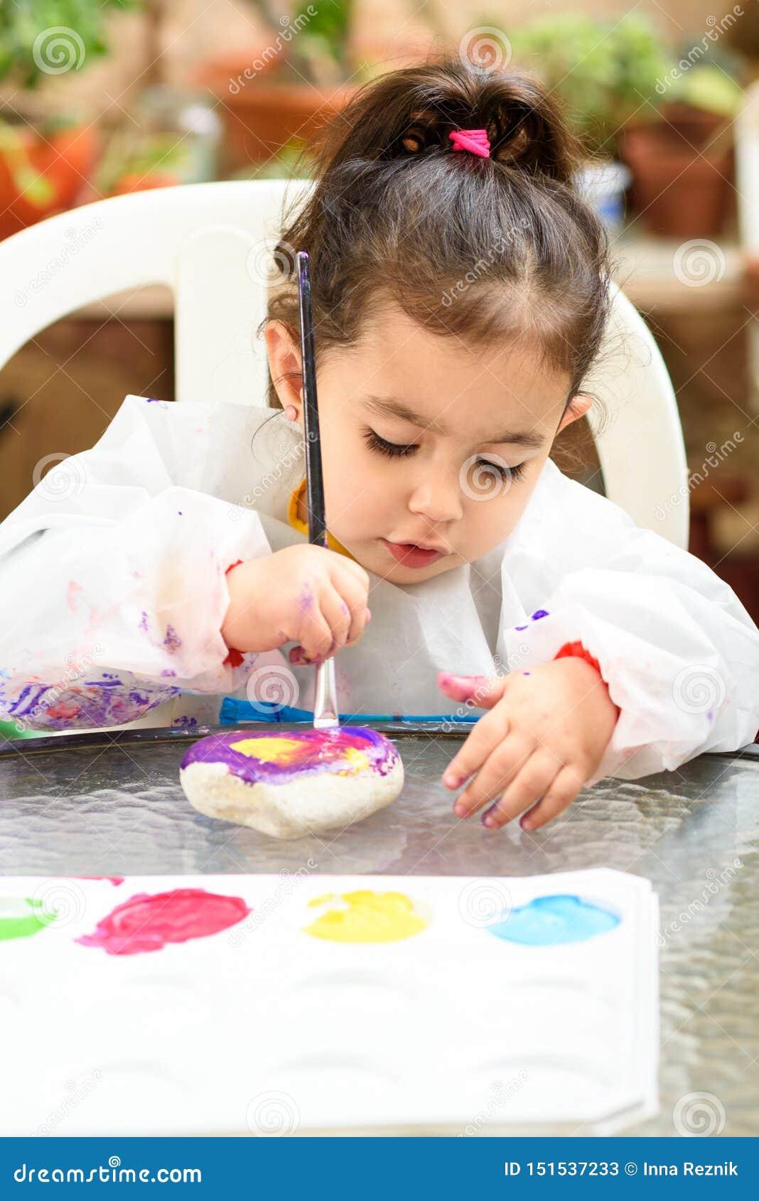 Gullig liten flicka som har roligt och att färga med borsten, att spela och att måla Förskolebarn med målarfärg på trädgården