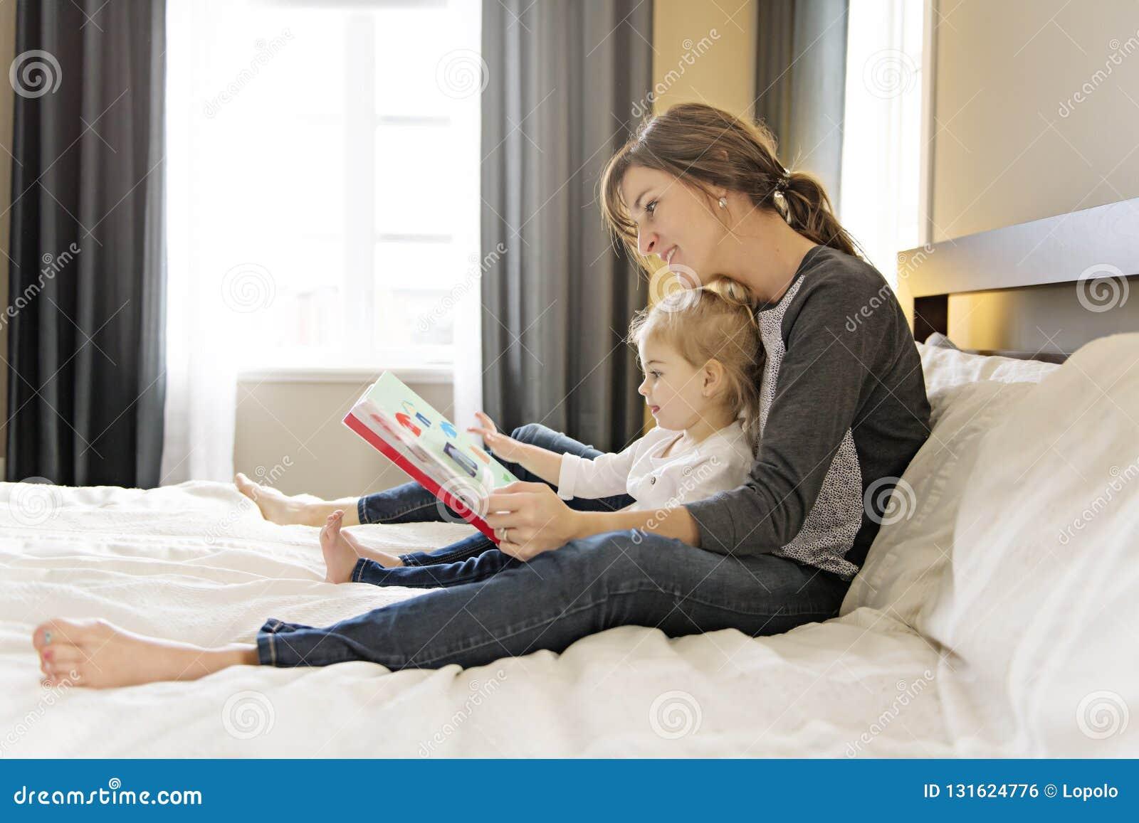 Gullig liten flicka som läser en bok med hennes moder i sovrummet