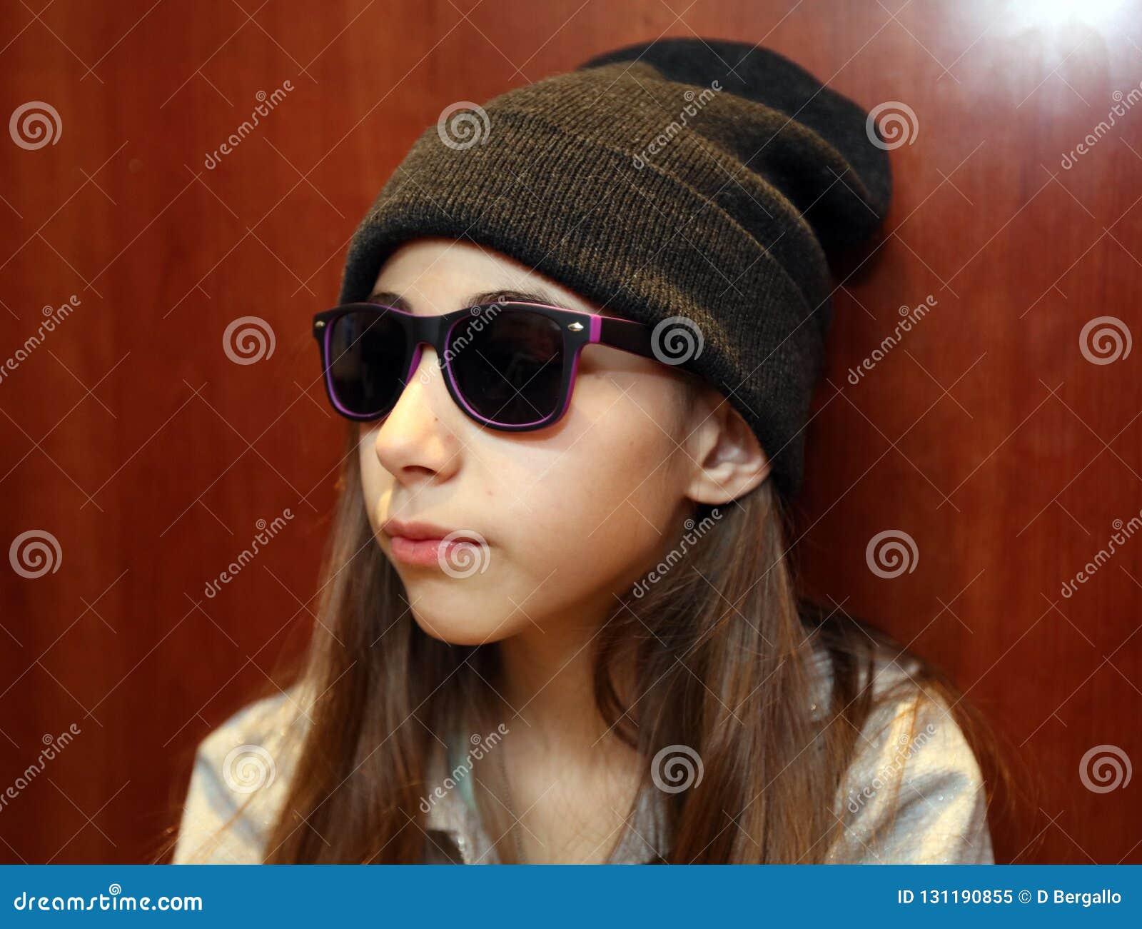 Gullig liten flicka som ler bära vit och svart solglasögon