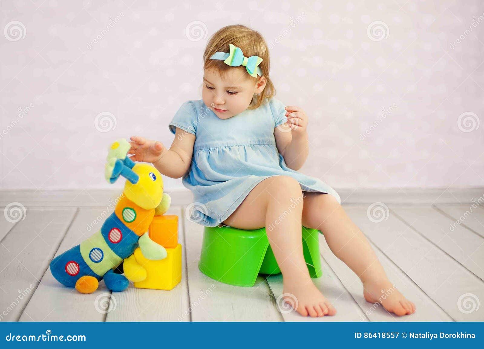 Gullig liten flickapotta som trainting med en leksak på huset